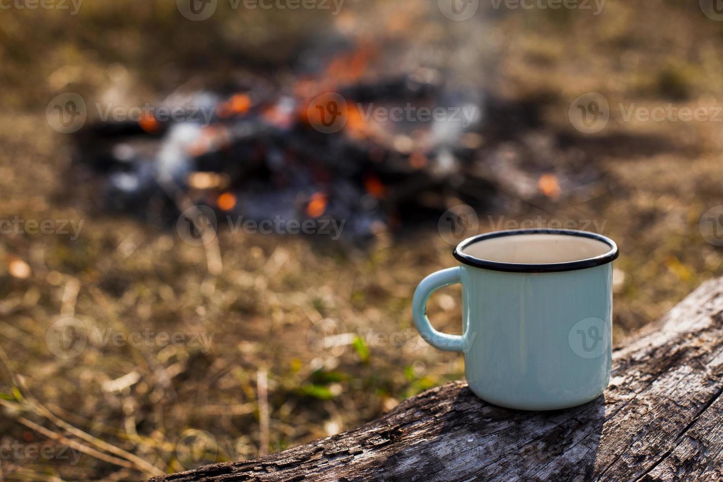 blauwe kop koffie bij het uitgebrande kampvuur foto