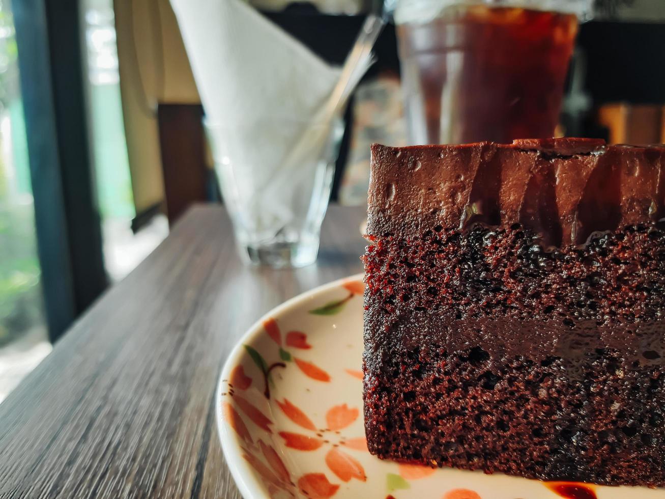bord met plakje lekkere zelfgemaakte chocoladetaart op tafel, heerlijke chocoladetaart. fluitje van een cent op een bord. zoet eten. zoet dessert. detailopname. foto