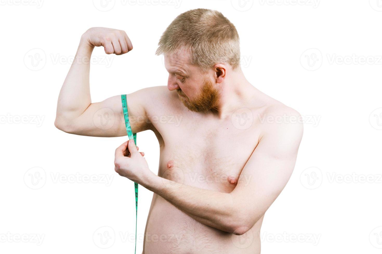 gefrustreerde bebaarde man die zijn biceps meet foto