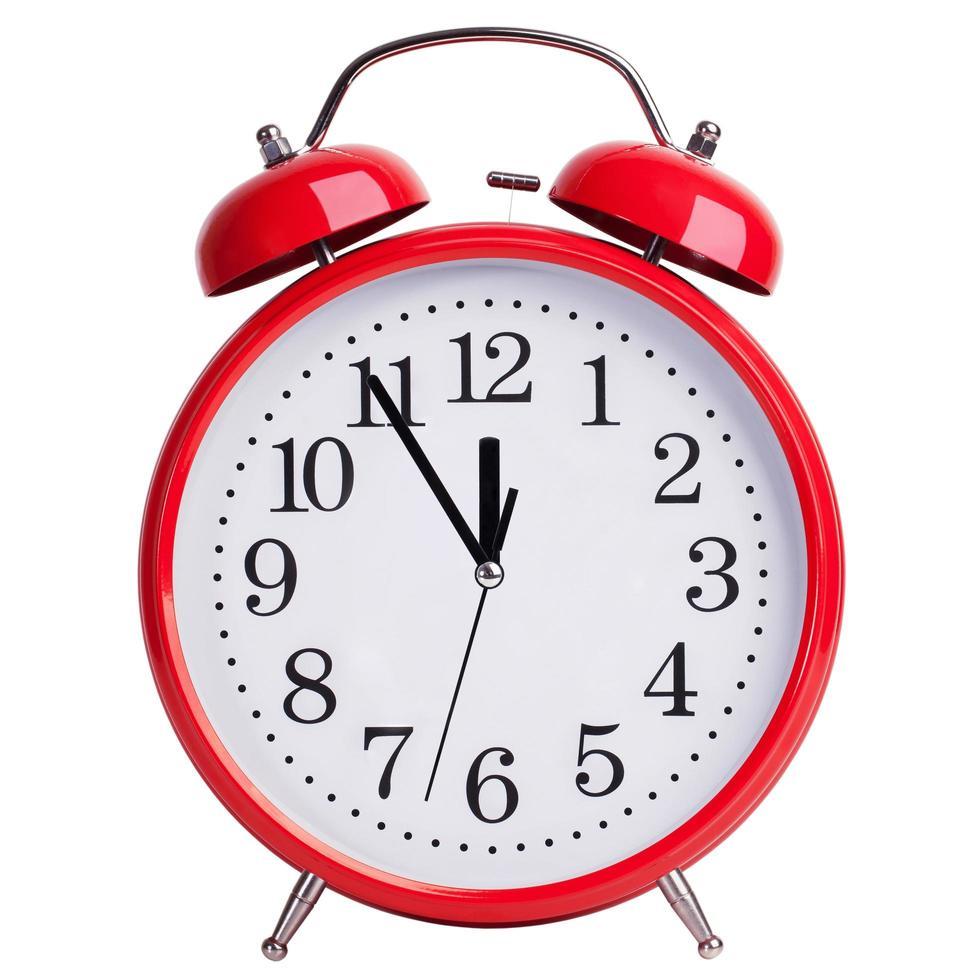 rode wekker toont vijf minuten voor twaalf foto