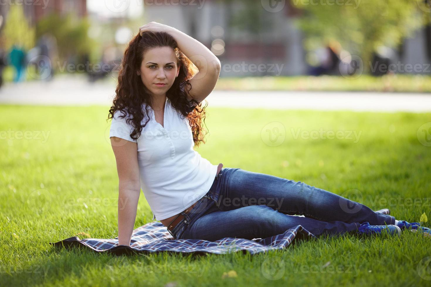 mooie vrouw in spijkerbroek zit op het gras foto