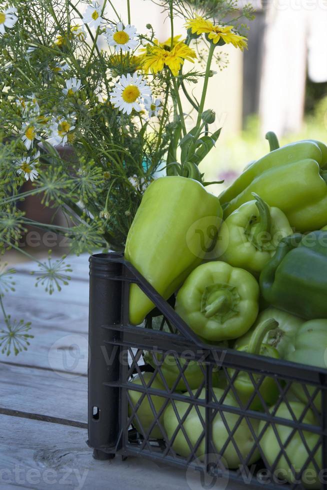groenten in een zwarte doos en een armvol wilde bloemen. verse groenten op een houten achtergrond. oogsten in de moestuin in de zomer. foto