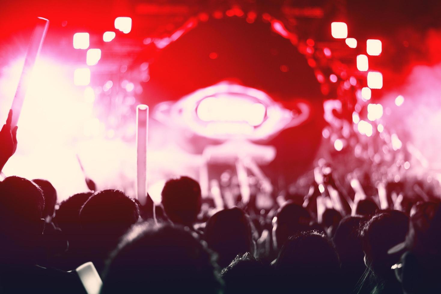 rockconcert met silhouetten mensen verhogen handvat concept. zanger en publiek thema. rode toon foto