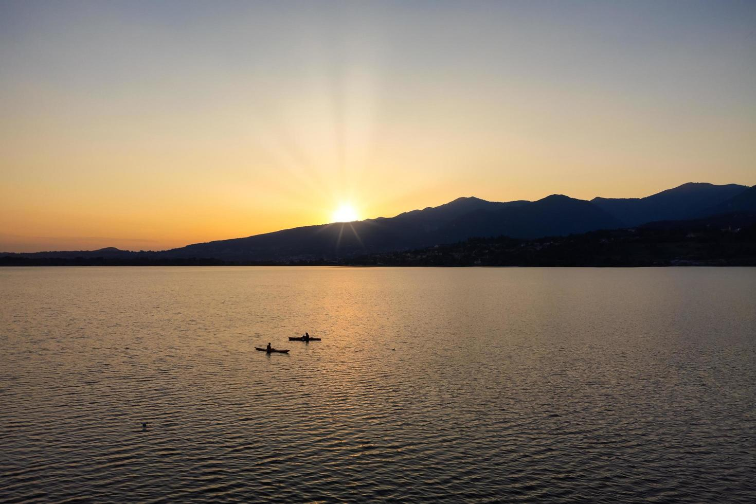 silhouet van twee kajaks midden op het meer bij zonsondergang foto