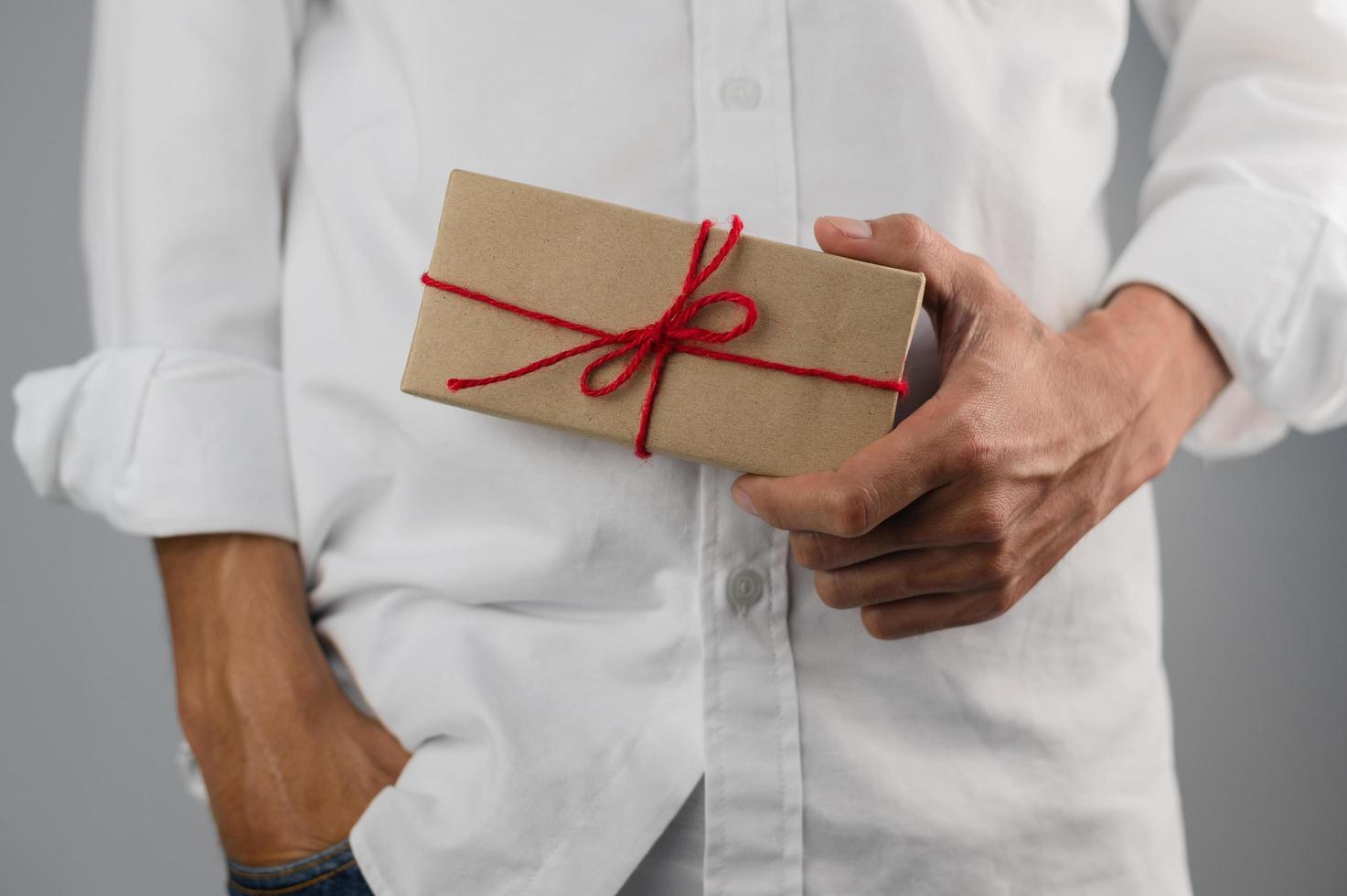 hand met geschenkdoos, nieuwjaarsgeschenkdoos, kerstcadeaudoos, kopieerruimte. Kerstmis, jaar, verjaardagsconcept. foto
