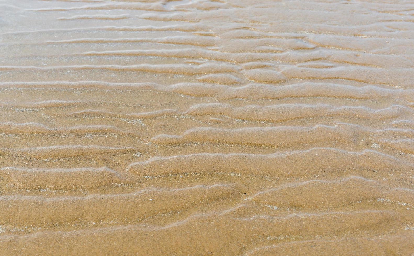 zand natuurtextuur.golf van zandtextuur dichtbij het strand foto