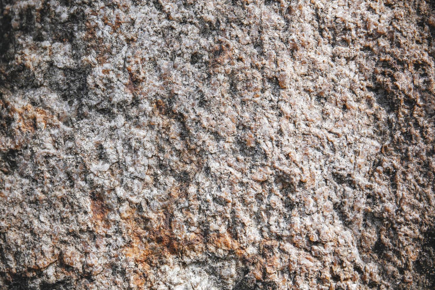 rustiek en ruw van donkerbruine stenen oppervlaktetextuur. foto