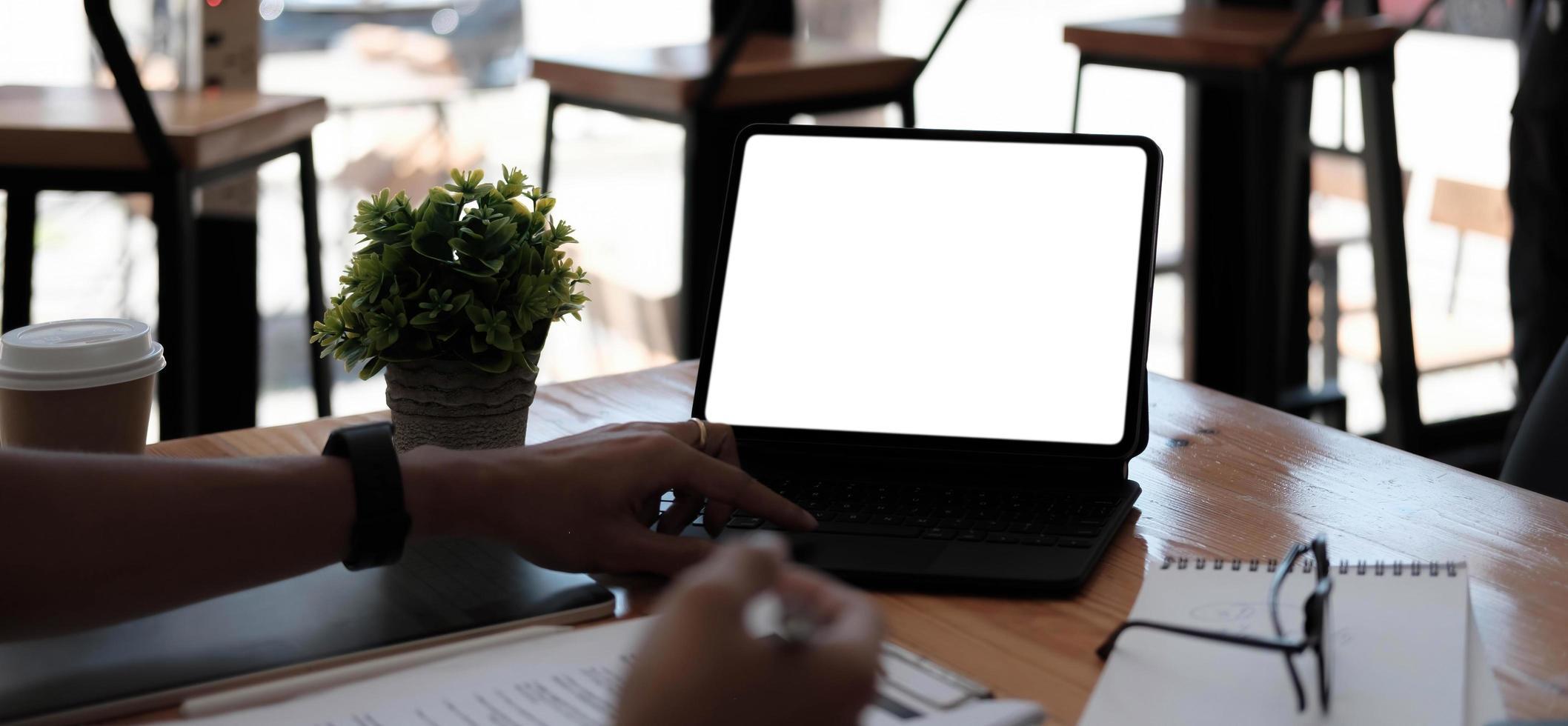zakenvrouw met behulp van laptop leeg scherm tijdens het werken met rekenmachine voor financiële. uitknippad foto