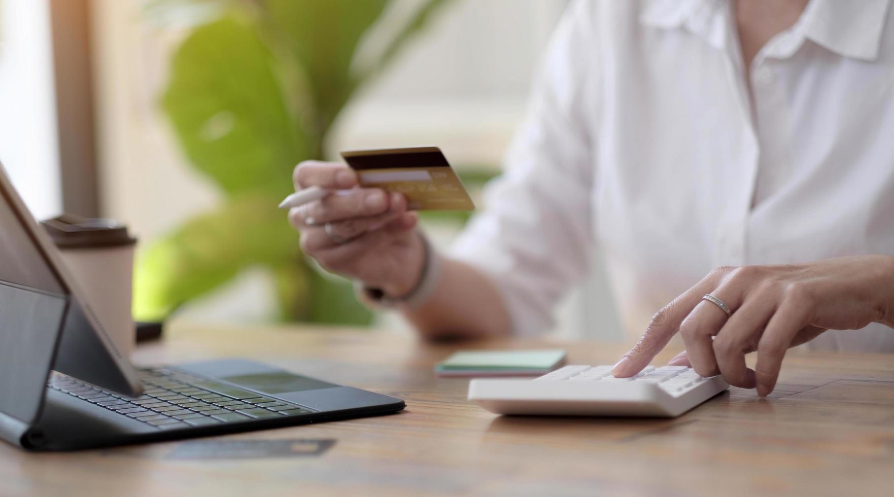 vrouw die berekeningen maakt en online winkelt met creditcard. vrouw met behulp van rekenmachine, budget en leenpapier op kantoor. rekeningen, huisbudget, belasting, sparen, financiën, economie, audit, schuldconcept foto