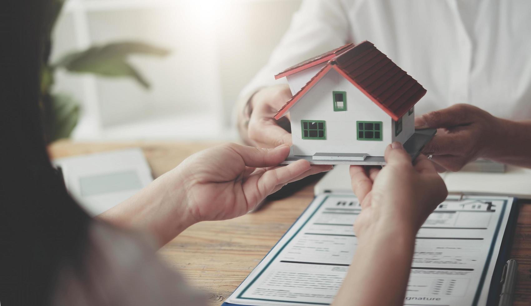 makelaar heeft het huis gegeven aan klanten die het huis hebben gekocht met verzekering, onderhandelen over koop-verkoop en investeringsplanningsconcept. foto