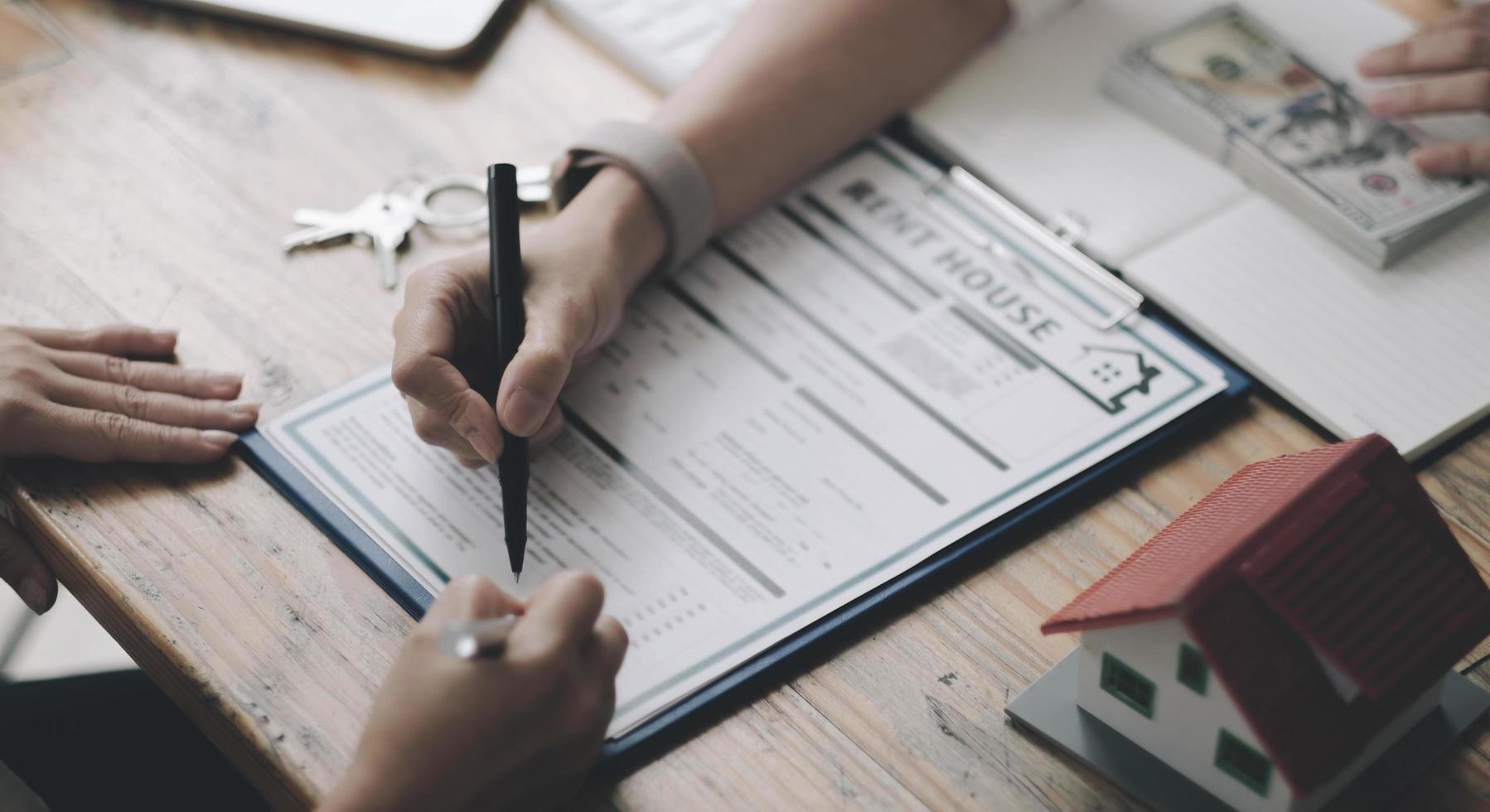 huismodel met agent en klant bespreken voor contract om onroerend goed of onroerend goed te kopen, verzekeringen of leningen te krijgen. foto