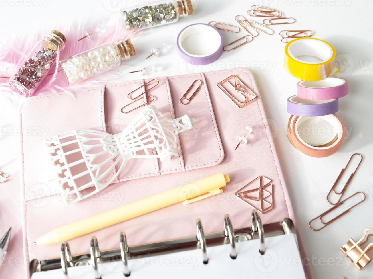 bovenaanzicht van een roze planner met schattig briefpapier. roze glamourplanner met een wit paspopbeeldje. planner met open pagina's op een witte achtergrond en met mooie accessoires pennen, knopen, pinnen. foto