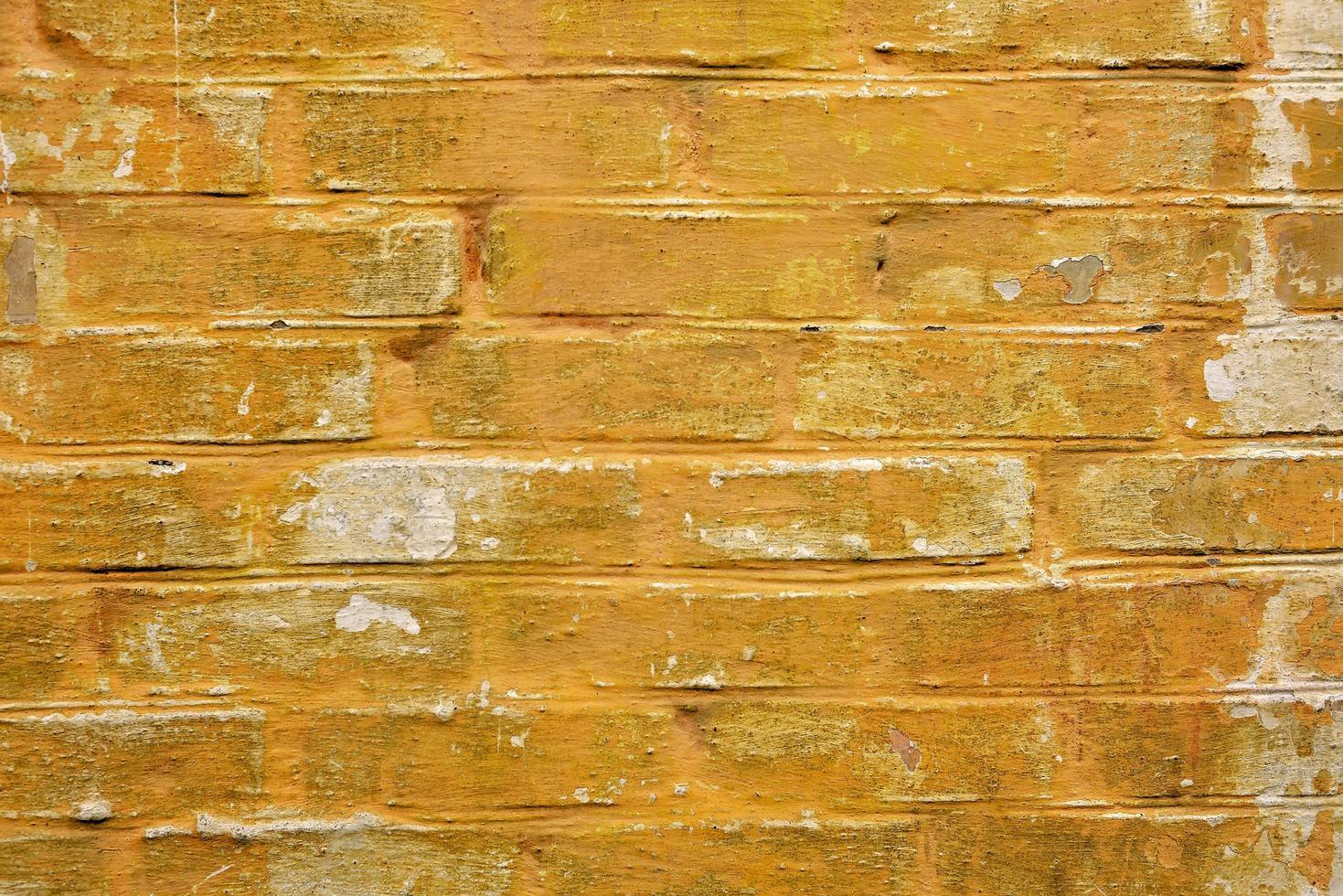ruwe gele bakstenen muur met afbladderende verf. textuur voor achtergrond foto