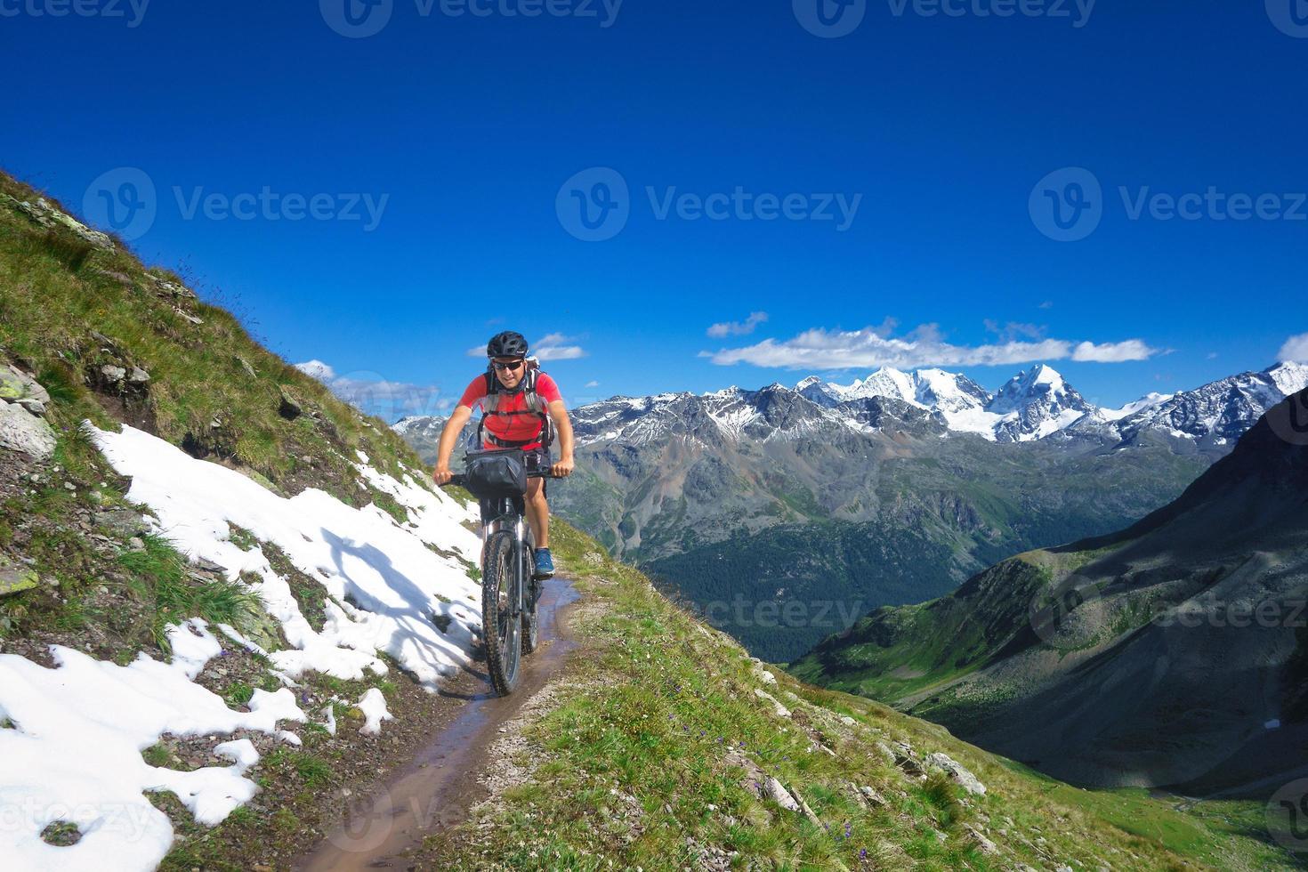 biker op bergpad in prachtig landschap op de alpen foto