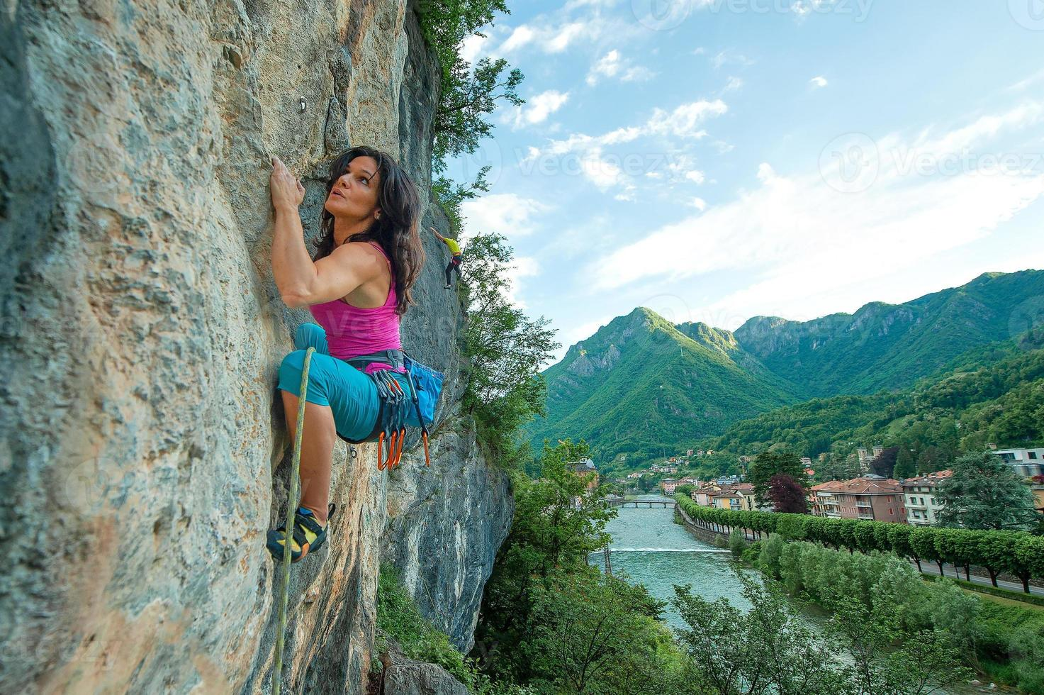 meisje oefent vrij klimmen op rots met panorama van het dorp foto