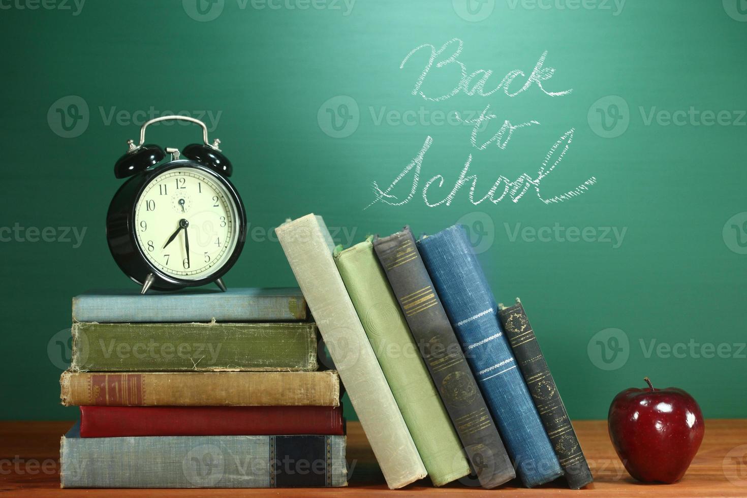 schoolboeken, appel en klok op bureau op school foto