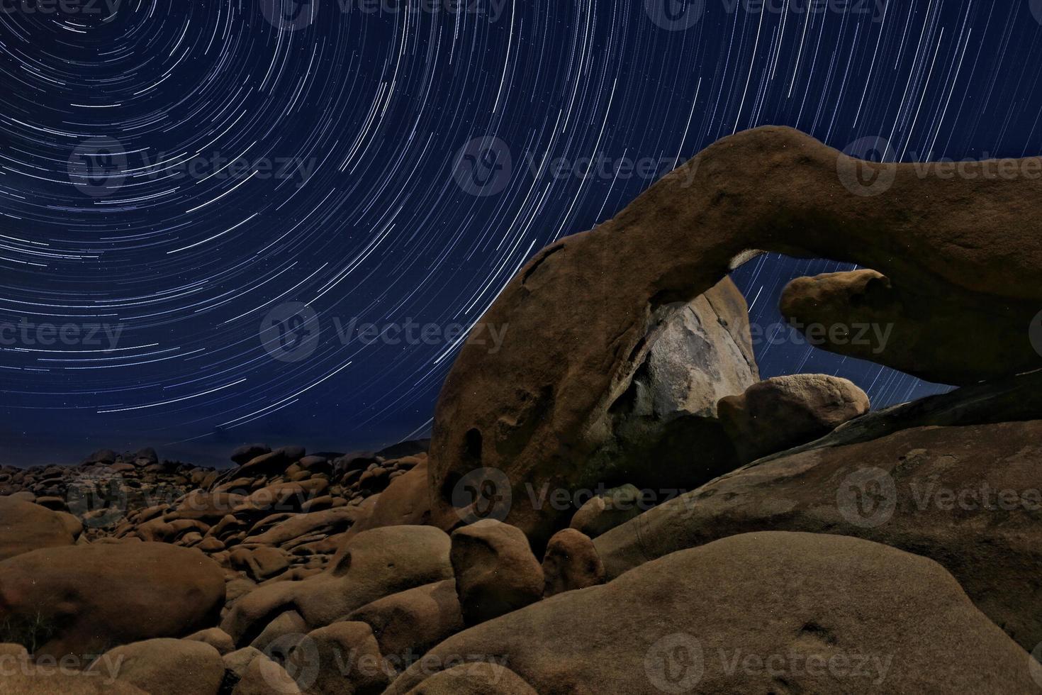 nachtsterspoor strijkt over de rotsen van joshua tree park foto