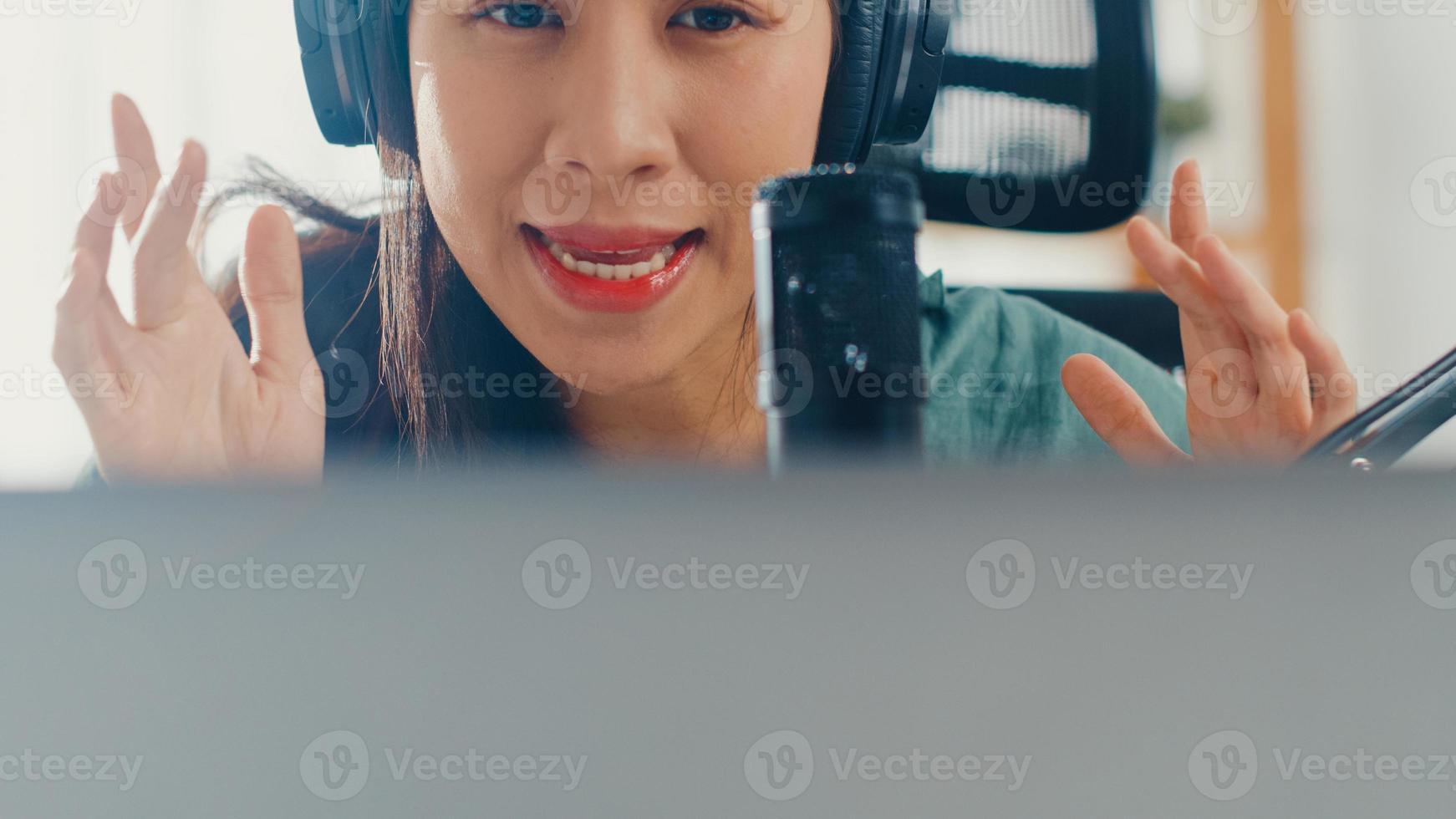 gelukkig aziatisch meisje neemt een podcast op haar laptopcomputer op met koptelefoon en microfoon praat met publiek in haar kamer. vrouwelijke podcaster maakt audiopodcast vanuit haar thuisstudio, verblijf in huisconcept. foto