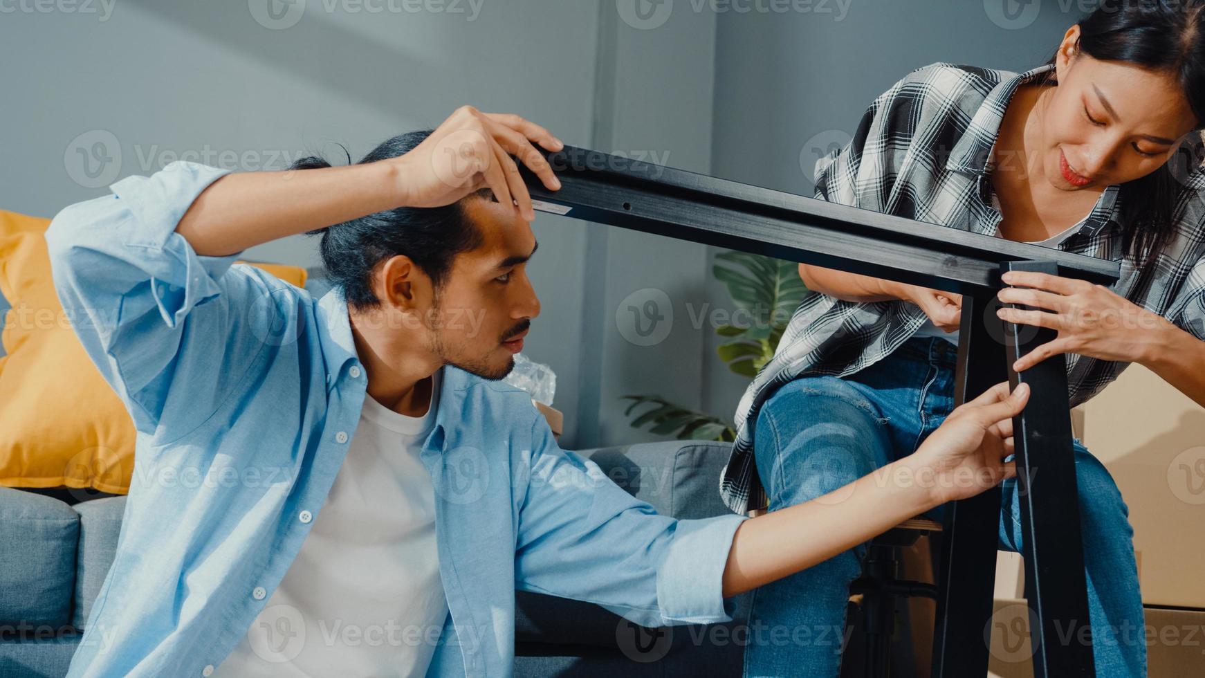 gelukkige Aziatische jonge aantrekkelijke paar man en vrouw helpen elkaar doos uitpakken en meubels monteren versieren huis bouwen tafel met kartonnen doos in de woonkamer. jong getrouwd aziatisch verhuisconcept. foto