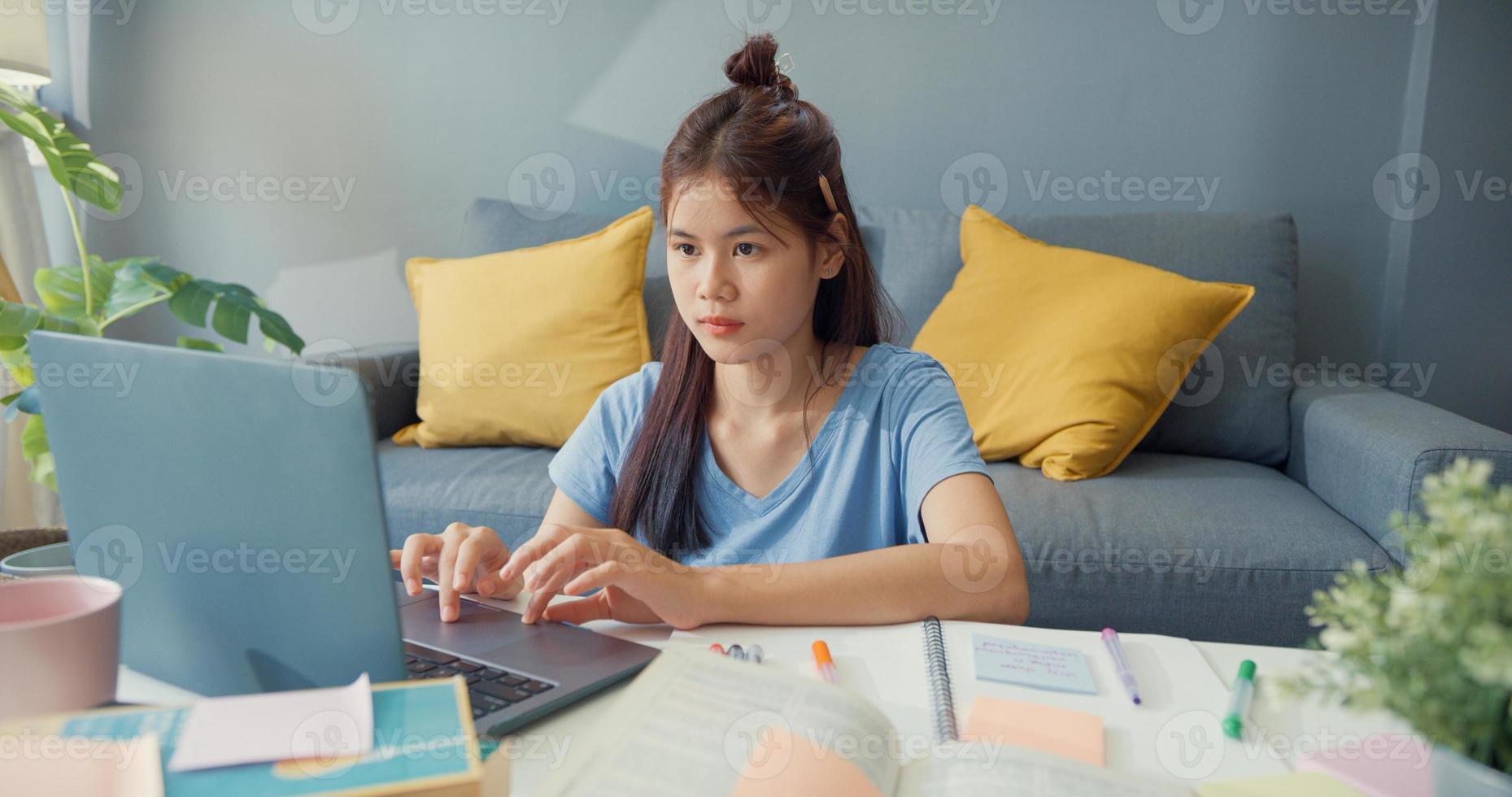 jonge Aziatische meisje tiener met casual gebruik laptopcomputer online leren schrijven college notebook voor de laatste test in de woonkamer thuis. isoleer onderwijs online e-learning coronavirus pandemie concept. foto