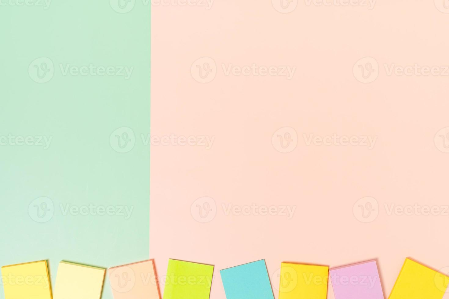 minimale werkruimte - creatieve platliggende foto van werkruimtebureau. bovenaanzicht bureau met zelfklevende notitie op pastel groen roze kleur achtergrond. bovenaanzicht met kopieerruimte, platliggende fotografie.