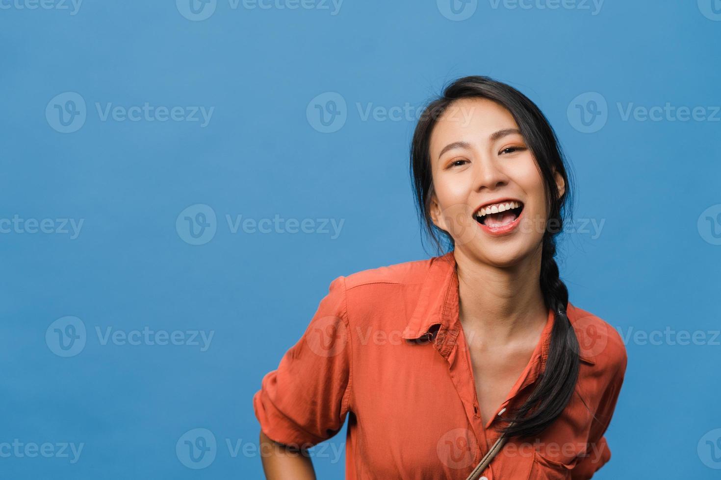 jonge azië dame met positieve uitdrukking, breed glimlachen, gekleed in casual kleding en camera kijken over blauwe achtergrond. gelukkige schattige blije vrouw verheugt zich over succes. gezichtsuitdrukking concept. foto