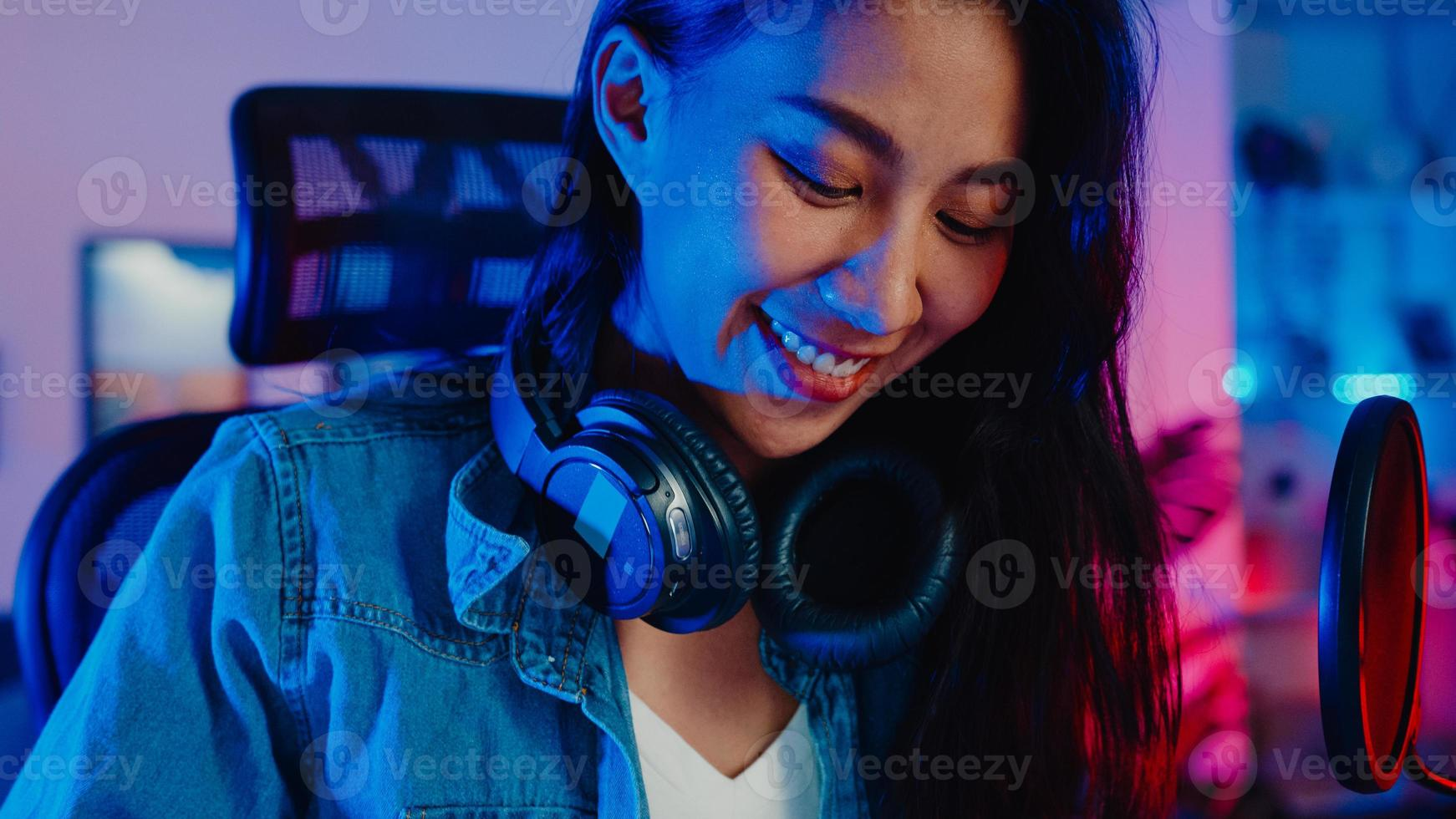 gelukkig azië meisje blogger spelen synthesizer toetsenbord dragen hoofdtelefoon en opnemen muziek met sound mixer op laptop in woonkamer thuisstudio 's nachts. maker van muziekinhoud, zelfstudie, uitzendconcept. foto
