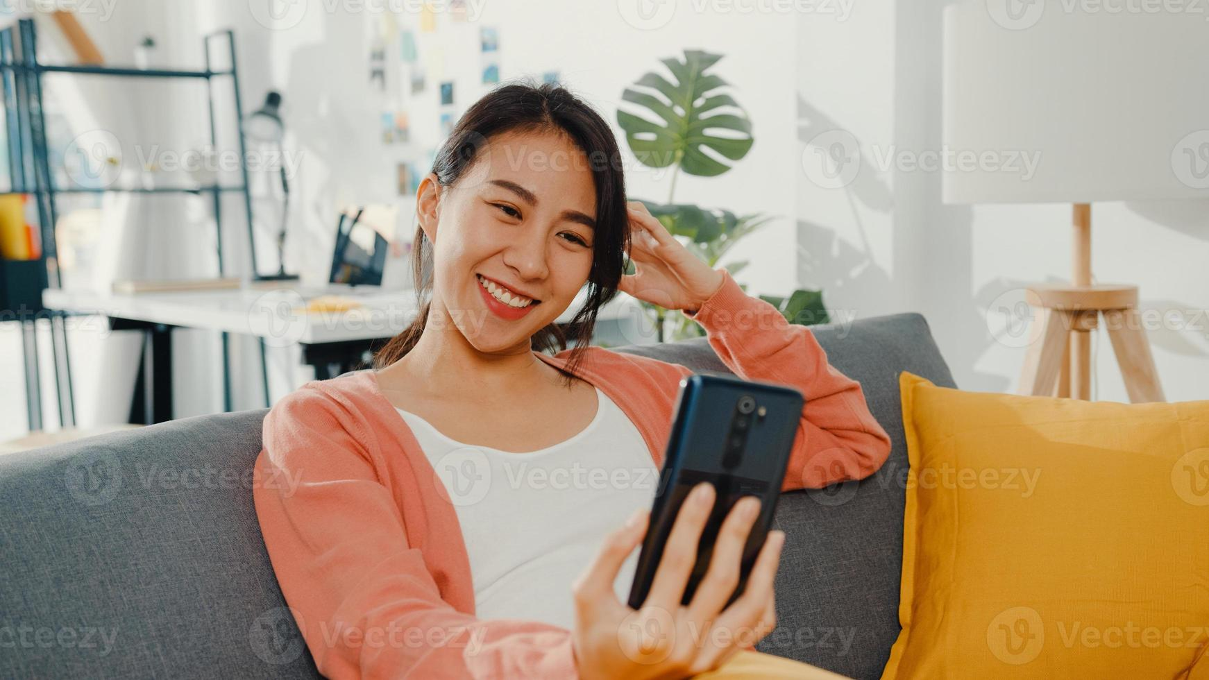 mooie aziatische dame glimlachend en zittend op de bank bel telefoongesprek zeg hallo met familie thuis. thuis blijven, langeafstandsrelatie, familierelatie, afstand houden, covid quarantaineconcept. foto