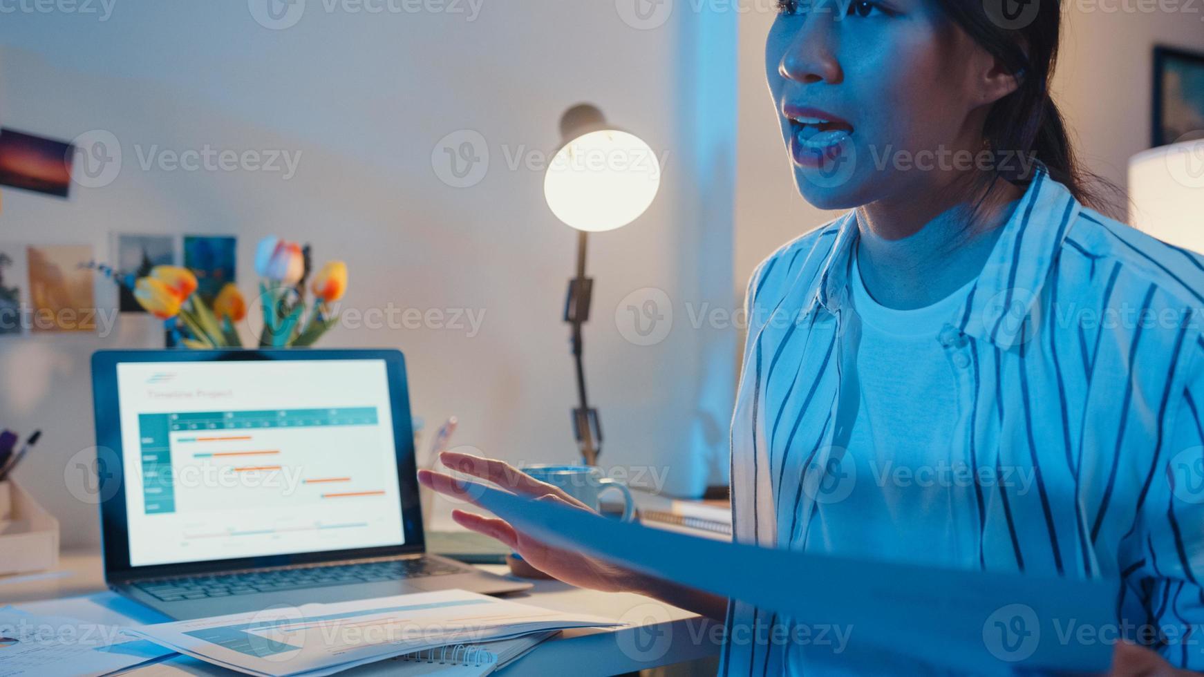 jonge azië zakenvrouw presentatie voorbereiden voor conferentie-interview op kantoor aan huis. 's nachts werken vanuit huis overbelasting, op afstand, sociale afstand, quarantaine voor preventie van het coronavirus. foto