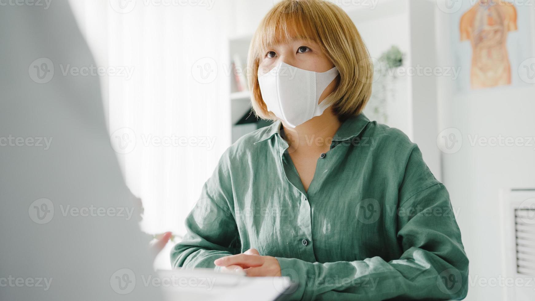 jonge aziatische dame arts draagt een beschermend masker met behulp van klembord levert geweldig nieuws, bespreek resultaten of symptomen met meisjespatiënt in het ziekenhuiskantoor. levensstijl nieuw normaal na corona virus. foto