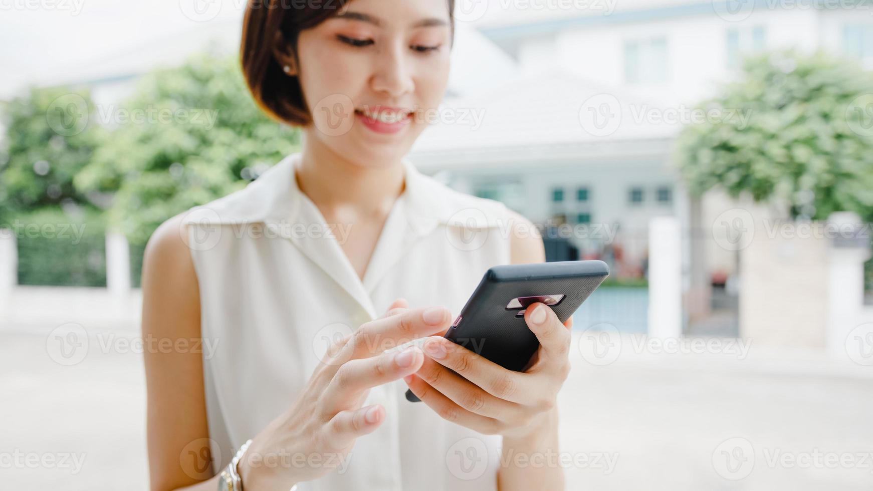 aantrekkelijke jonge azië zakenvrouw met behulp van mobiele telefoon sociale media internet te controleren, chatten met vrienden buiten op straat in de stad. levensstijl nieuw normaal na coronavirus en sociale afstand. foto