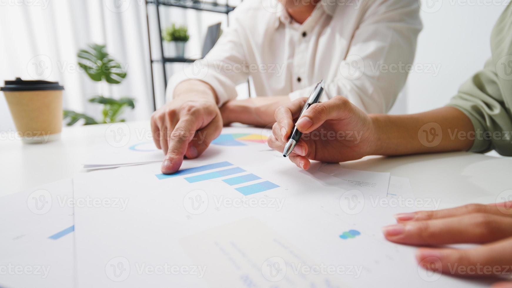 gelukkige jonge Aziatische zakenlieden en zakenvrouwen ontmoeten brainstormideeën over nieuwe papierwerkprojectcollega's die samenwerken bij het plannen van successtrategie genieten van teamwork in een klein modern kantoor. foto