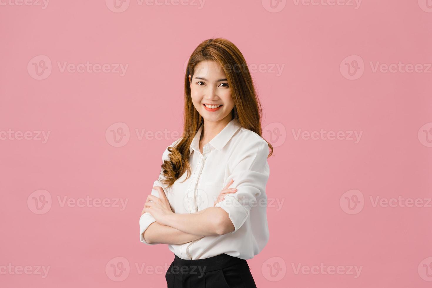 portret van jonge Aziatische dame met positieve uitdrukking, armen gekruist, breed glimlachen, gekleed in casual kleding en camera kijken over roze achtergrond. gelukkige schattige blije vrouw verheugt zich over succes. foto