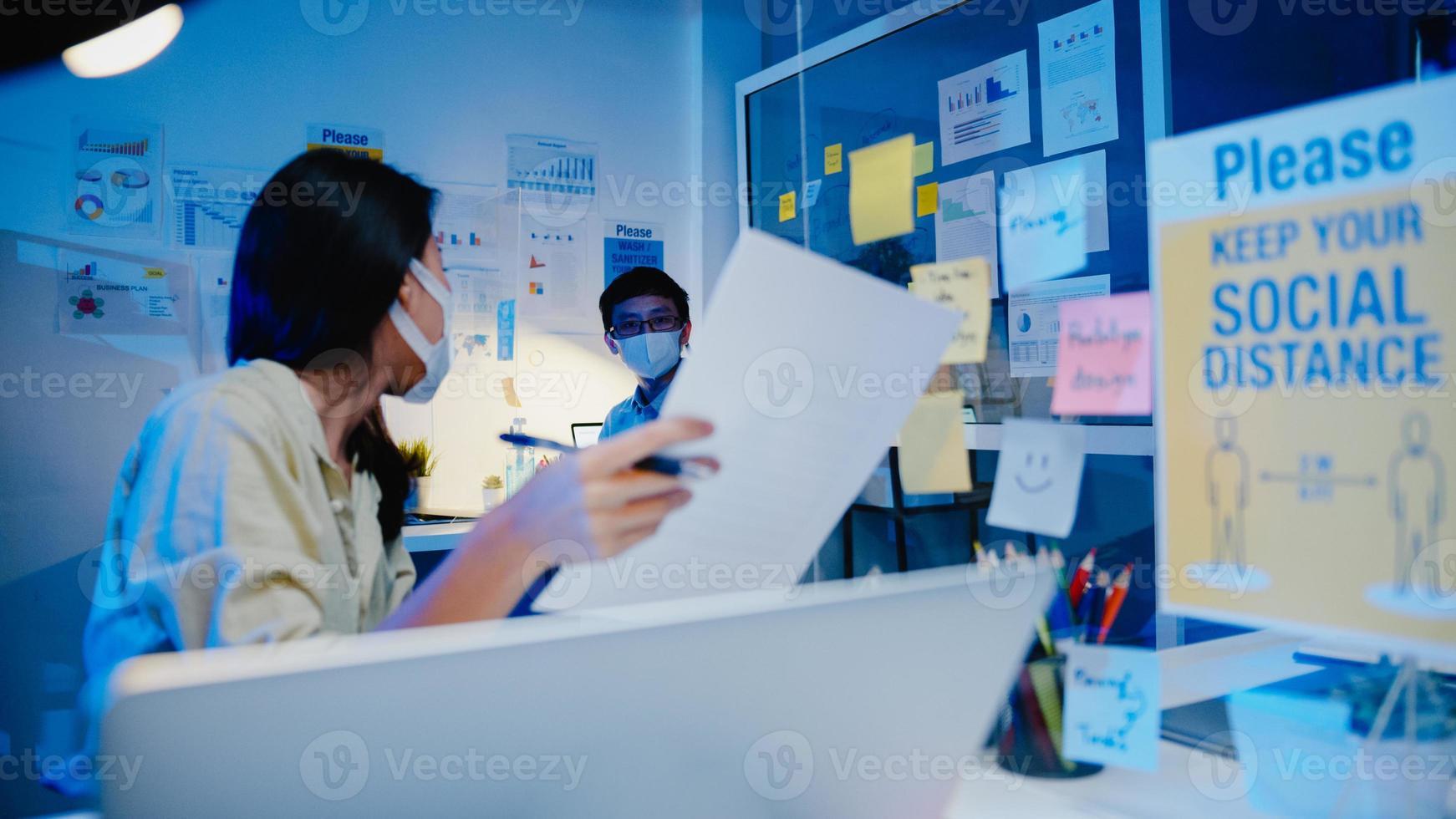 gelukkige zakenvrouw in Azië draagt gezichtsmasker voor sociale afstand in nieuwe normale situatie voor viruspreventie tijdens het bespreken van zakelijke brainstormbijeenkomsten samen delen gegevens terug op het werk in de kantoornacht foto