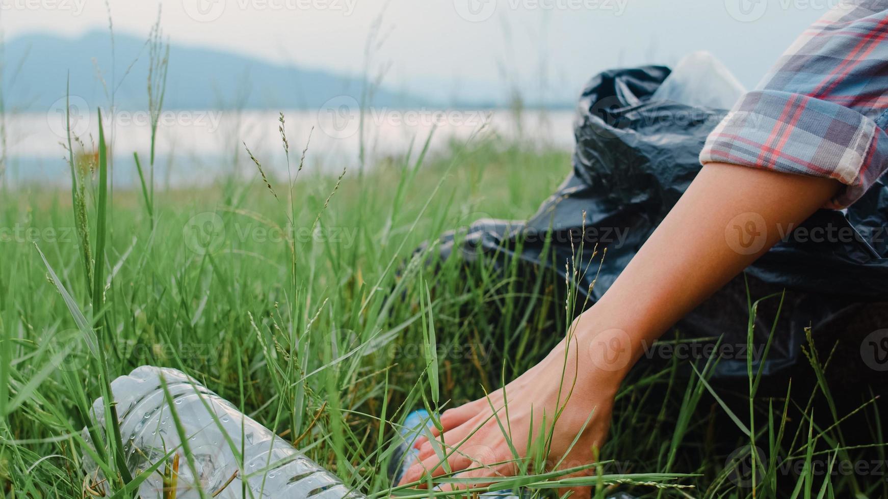 gelukkige jonge azië-activisten die plastic afval in het bos verzamelen. Koreaanse vrouwelijke vrijwilligers helpen de natuur schoon te houden en vuilnis op te halen. concept over milieubehoud vervuilingsproblemen. foto