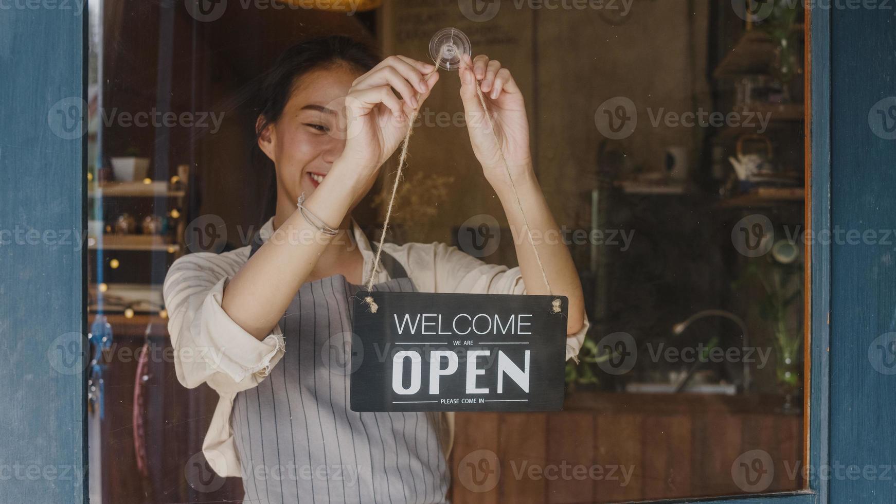 jong aziatisch managermeisje verandert een bord van gesloten naar open bord op deurcafé dat naar buiten kijkt en wacht op klanten na afsluiting. eigenaar klein bedrijf, eten en drinken, bedrijf heropenen opnieuw concept. foto