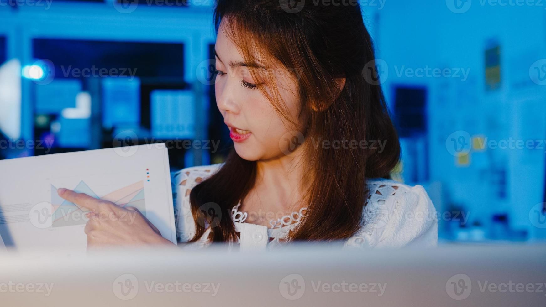 Azië zakenvrouw sociale afstand in het nieuwe normaal voor viruspreventie kijken naar camerapresentatie aan collega over plan in videogesprek tijdens het werk in kantoornacht. levensstijl na het coronavirus. foto