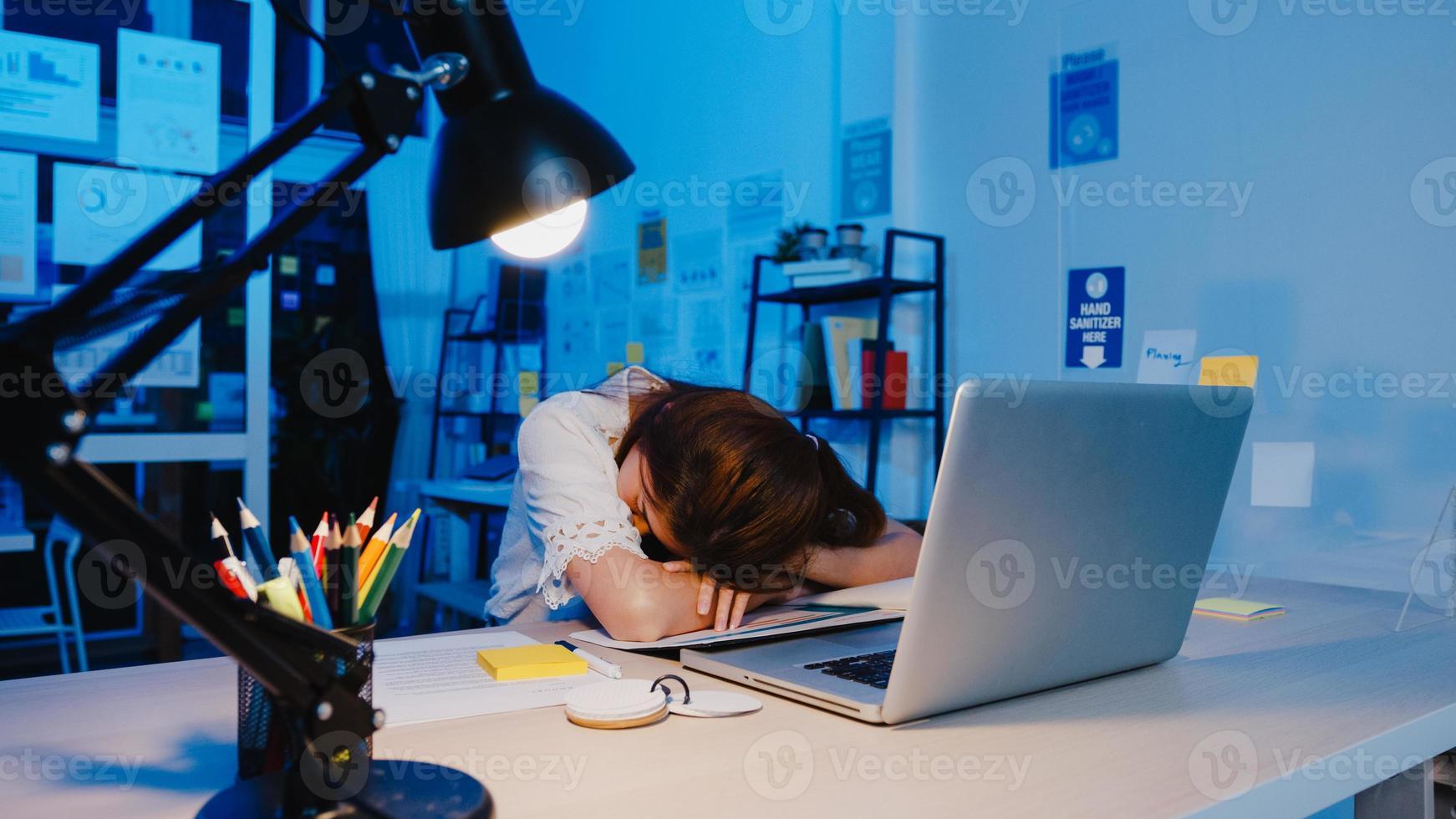 freelance azië uitgeputte dame hard werken slapen op nieuw normaal thuiskantoor. 's nachts thuiswerken overbelasting, op afstand, zelfisolatie, sociale afstand, quarantaine voor preventie van het coronavirus. foto