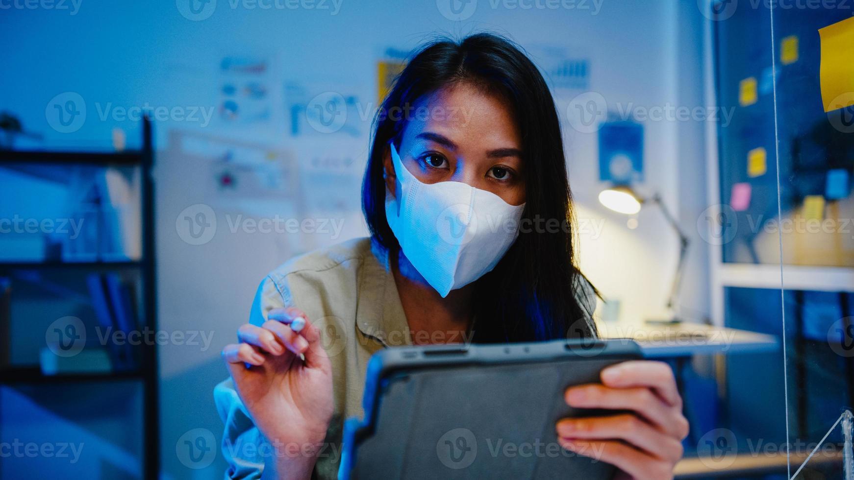 azië zakenvrouw draagt gezichtsmasker sociale afstand in situatie voor viruspreventie kijken naar camerapresentatie aan vrienden over plan in videogesprek terwijl ze op kantoor werken. leven na corona. foto