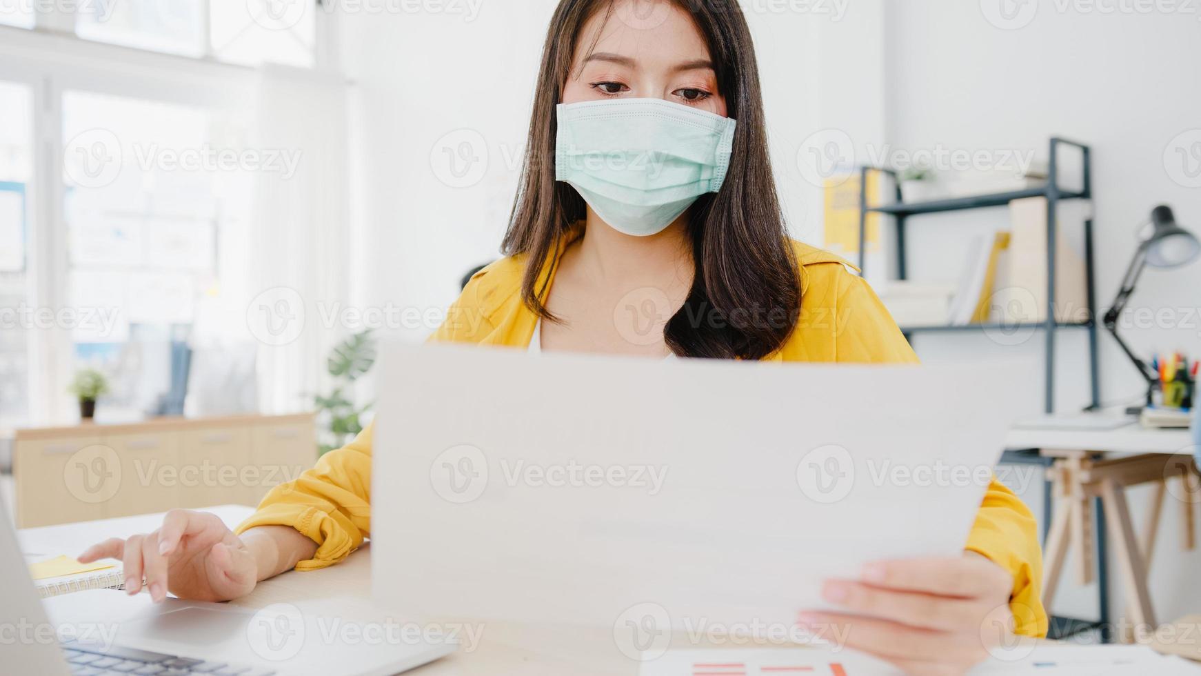 azië zakenvrouw ondernemer met medisch gezichtsmasker voor sociale afstand in nieuwe normale situatie voor viruspreventie tijdens het gebruik van laptop terug op het werk op kantoor. levensstijl na het coronavirus. foto