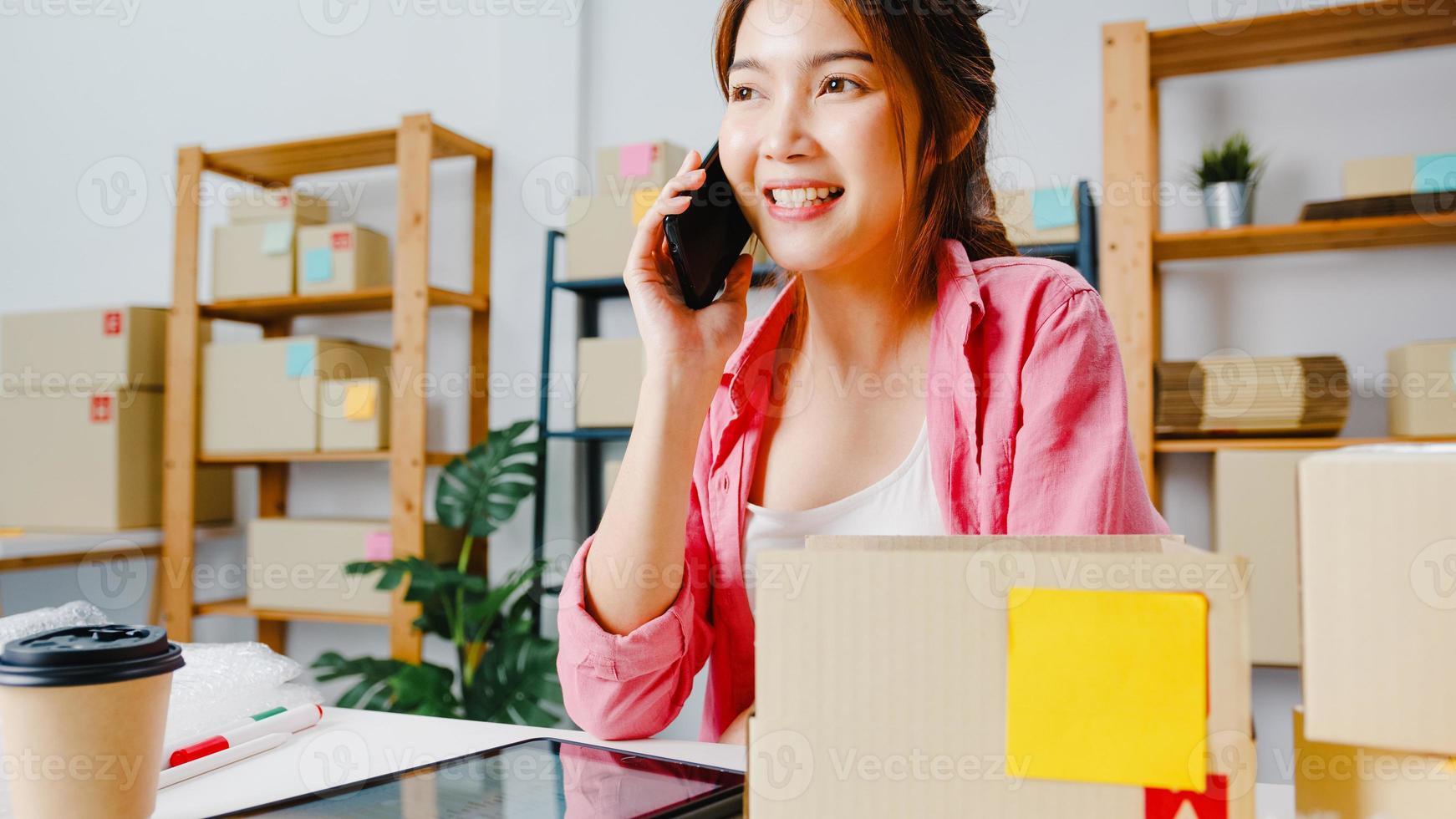 jonge azië zakenvrouw met behulp van mobiel telefoongesprek ontvangen inkooporder en product op voorraad controleren, werken op kantoor aan huis. eigenaar van een klein bedrijf, online marktlevering, lifestyle freelance concept. foto