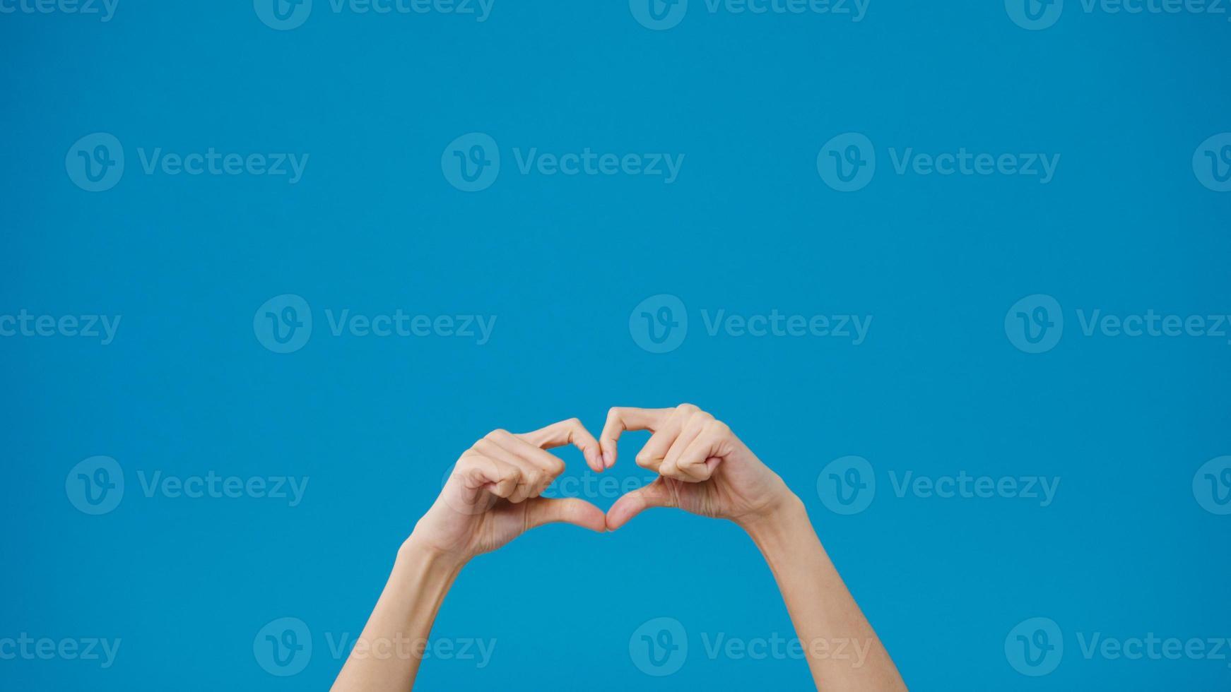 de hand van de jonge vrouw toont het maken van de vorm van een hart dat liefde naar haar minnaar stuurt over een blauwe achtergrond. kopieer ruimte voor het plaatsen van een tekst, bericht voor reclame. advertentiegebied, mockup promotionele inhoud. foto