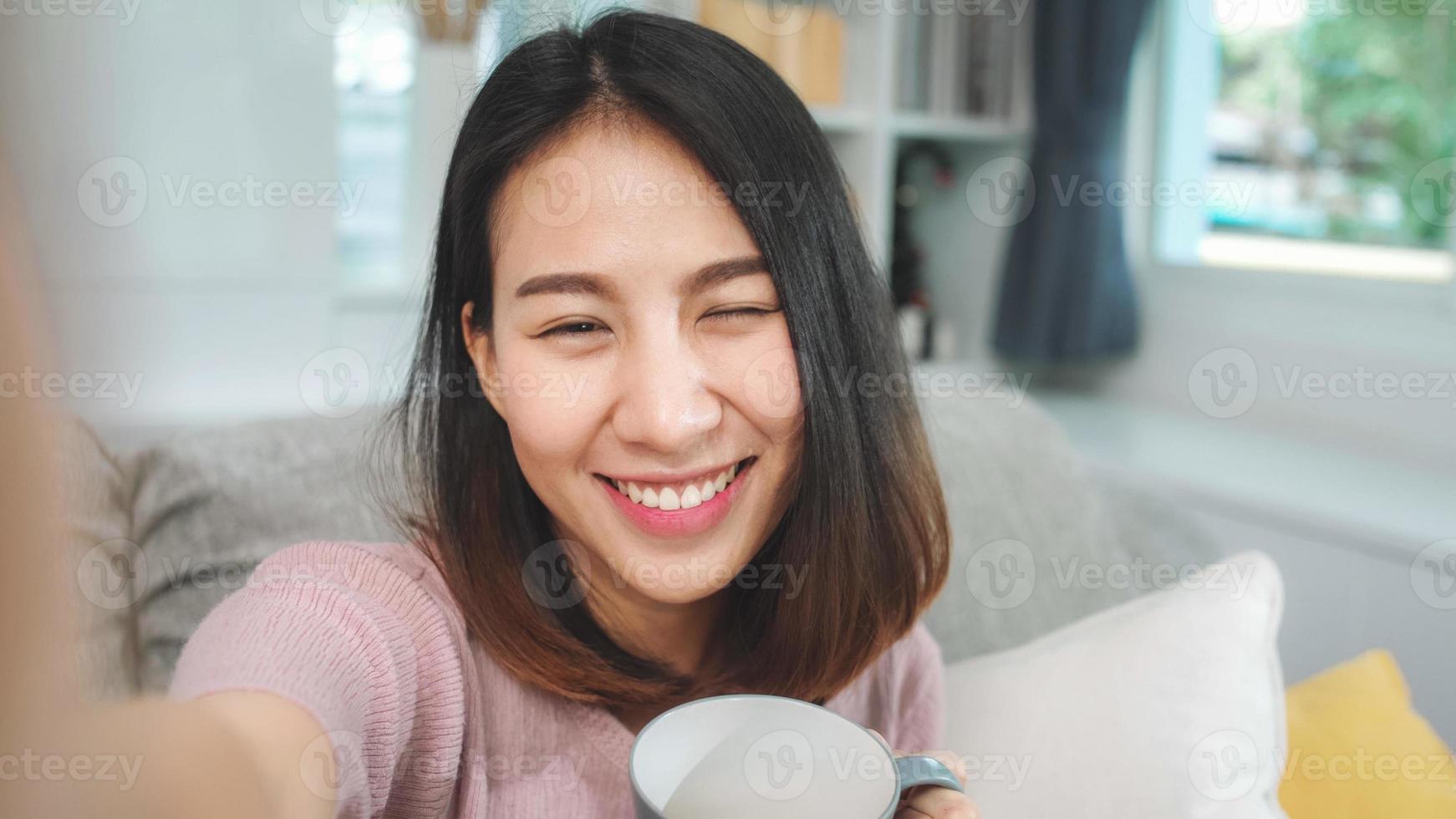jonge aziatische tienervrouw vlog thuis, vrouw drinkt koffie en gebruikt een smartphone die vlog-video maakt naar sociale media in de woonkamer. levensstijl vrouw ontspannen in de ochtend thuis concept. foto