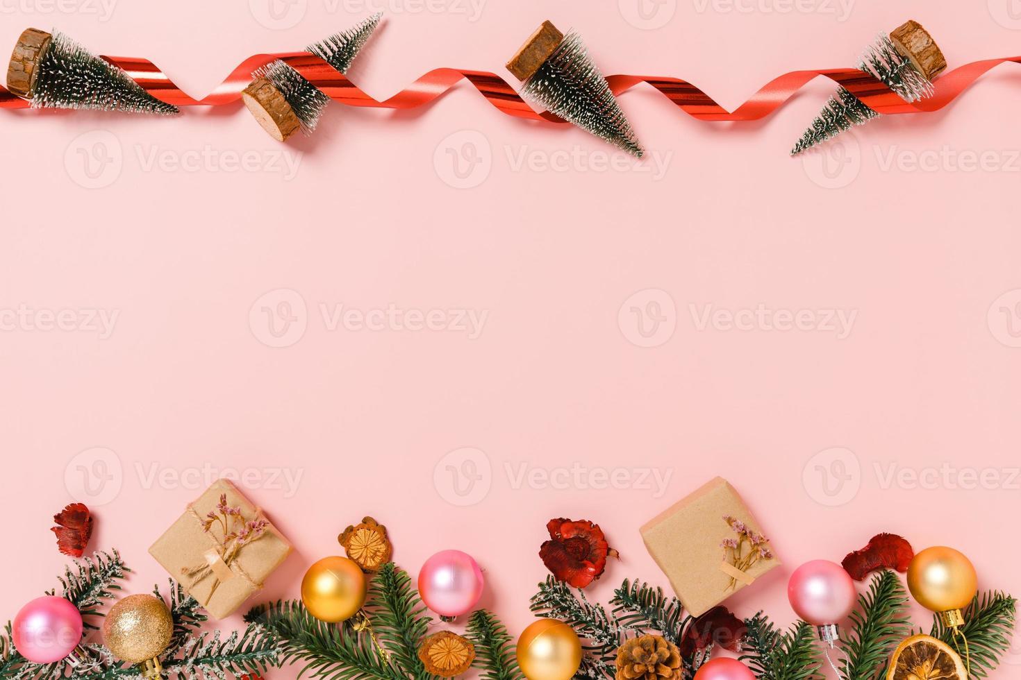 minimale creatieve platte lay van traditionele kerstcompositie en nieuwjaarsvakantieseizoen. bovenaanzicht winter kerstversiering op roze achtergrond met lege ruimte voor tekst. kopieer ruimtefotografie. foto
