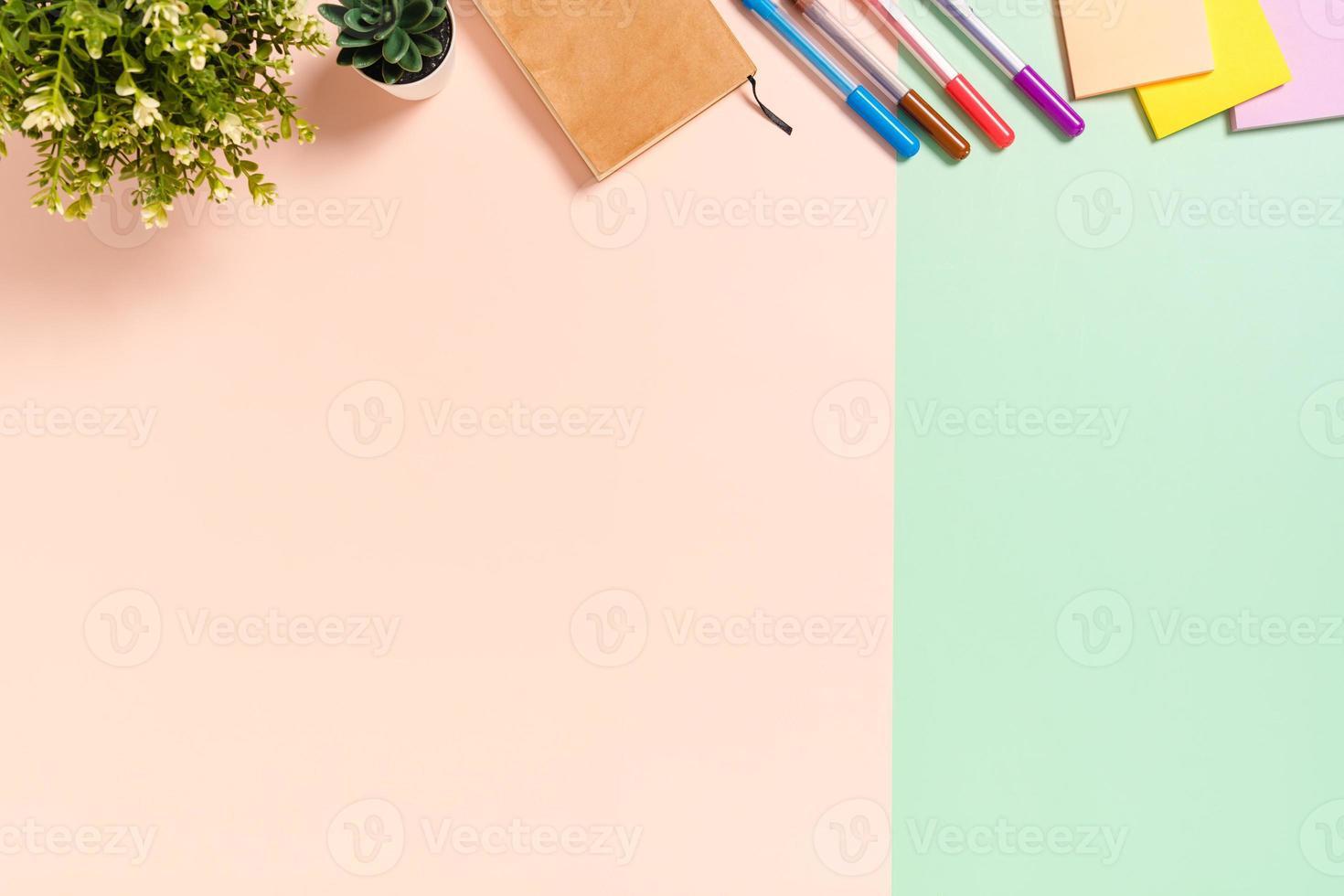 minimale werkruimte - creatieve platliggende foto van werkruimtebureau. bovenaanzicht bureau met zelfklevende notitie en notitieboekje op pastel groen roze kleur achtergrond. bovenaanzicht met kopie ruimtefotografie.