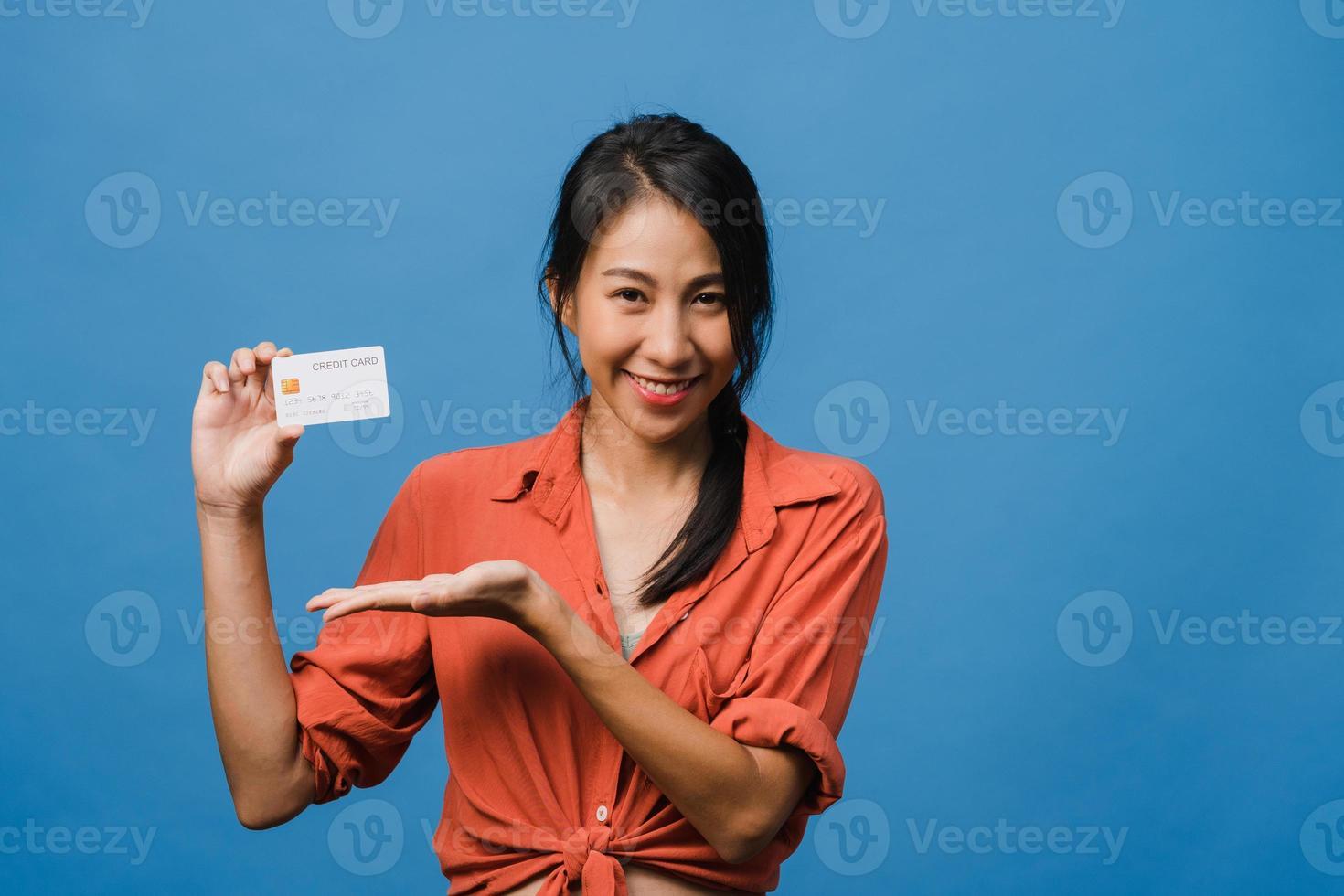 jonge aziatische dame toont creditcard met positieve uitdrukking, glimlacht breed, gekleed in casual kleding die geluk voelt en staat geïsoleerd op blauwe achtergrond. gezichtsuitdrukking concept. foto