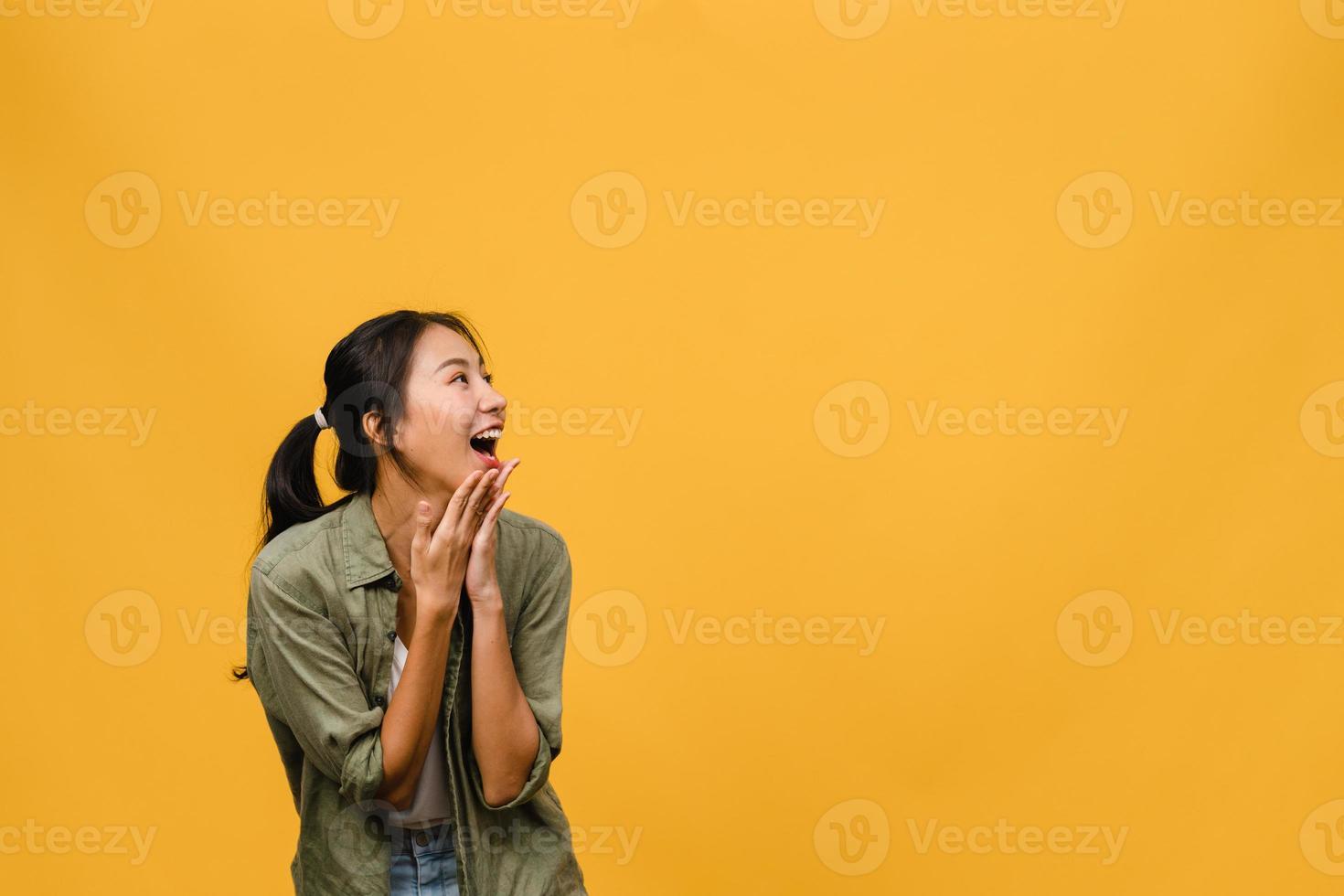 jonge aziatische dame voelt geluk met positieve uitdrukking, vrolijke verrassing funky, gekleed in casual doek geïsoleerd op gele achtergrond. gelukkige schattige blije vrouw verheugt zich over succes. gezichtsuitdrukking. foto