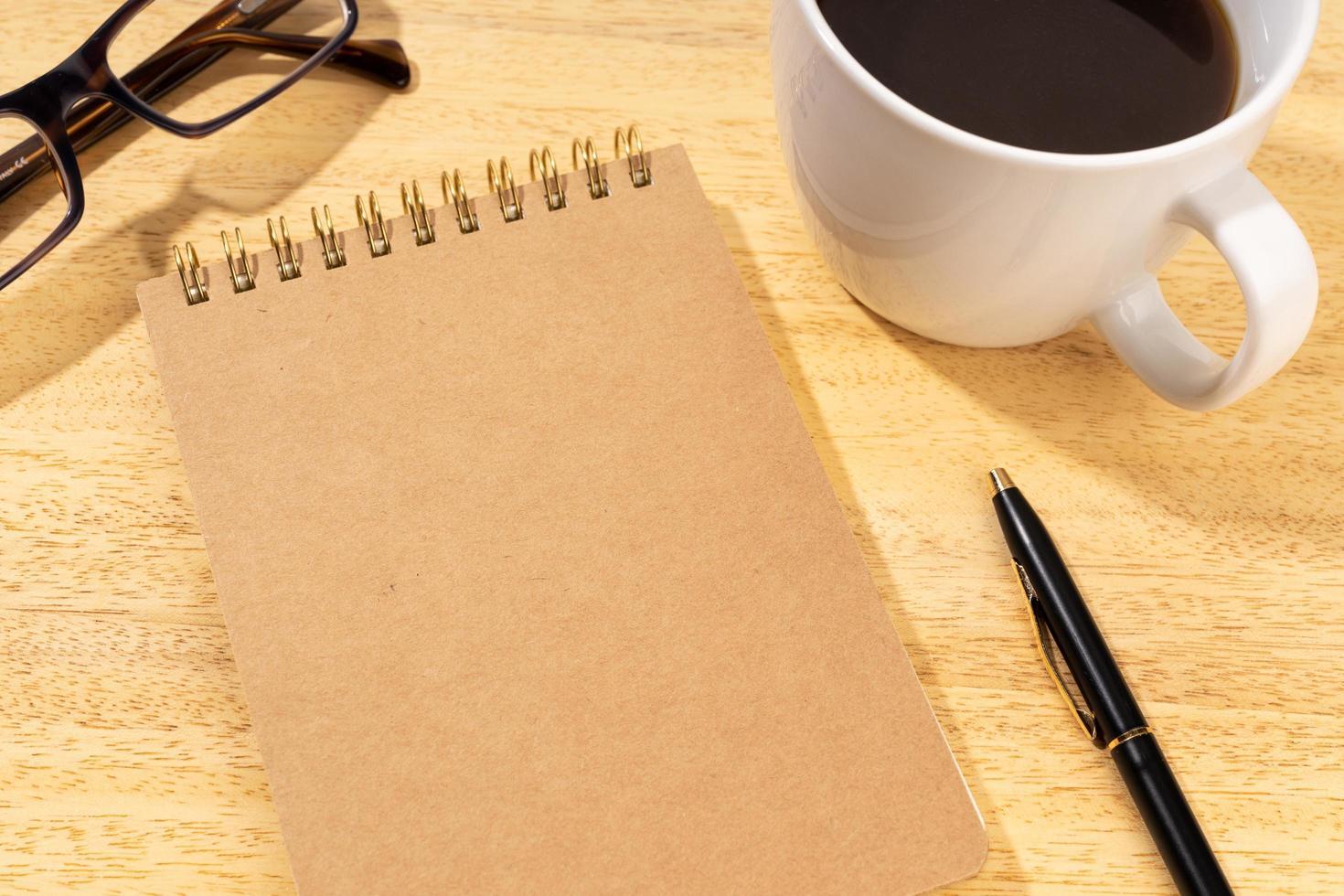 lege kartonnen notitieblok op houten bureau met kopje koffie en bril. sjabloon mock-up foto