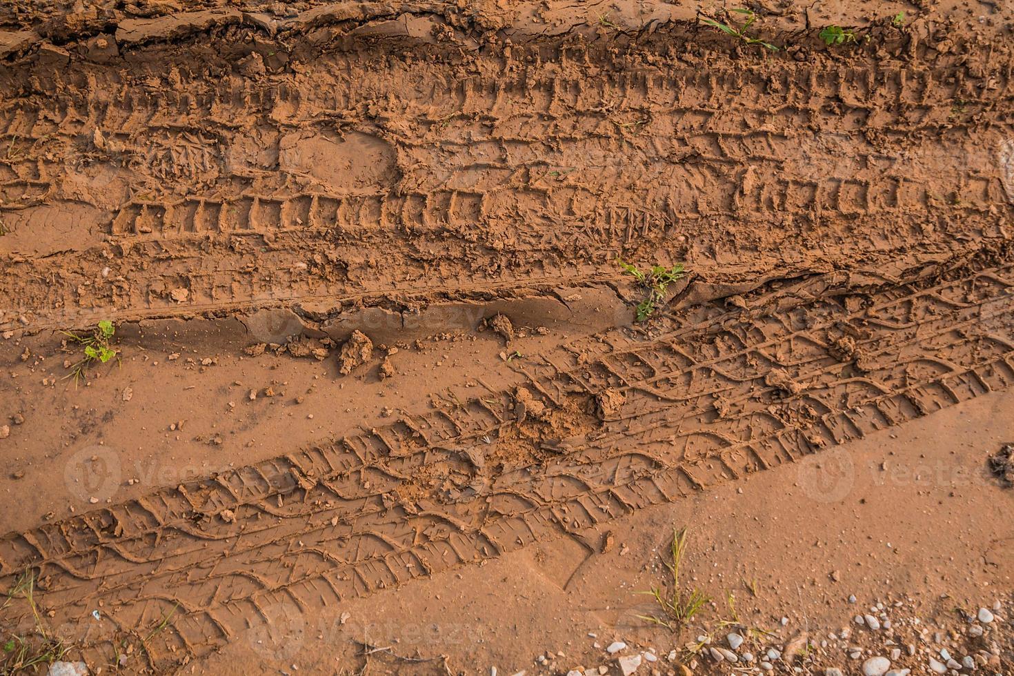 textuur van natte bruine modder met autobandsporen en schoenvoetafdruk foto