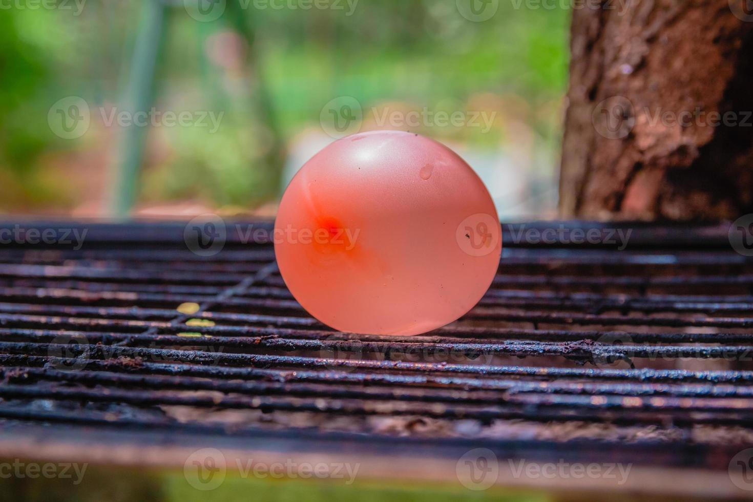 ballon gevuld met water geplaatst op een hete grill foto